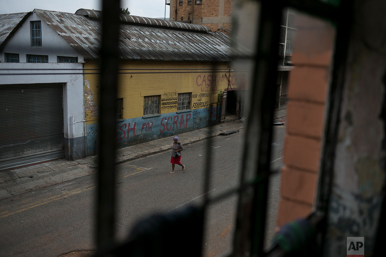 A woman walks past an abandoned building occupied by squatters. March 30, 2018. (AP Photo/Bram Janssen)