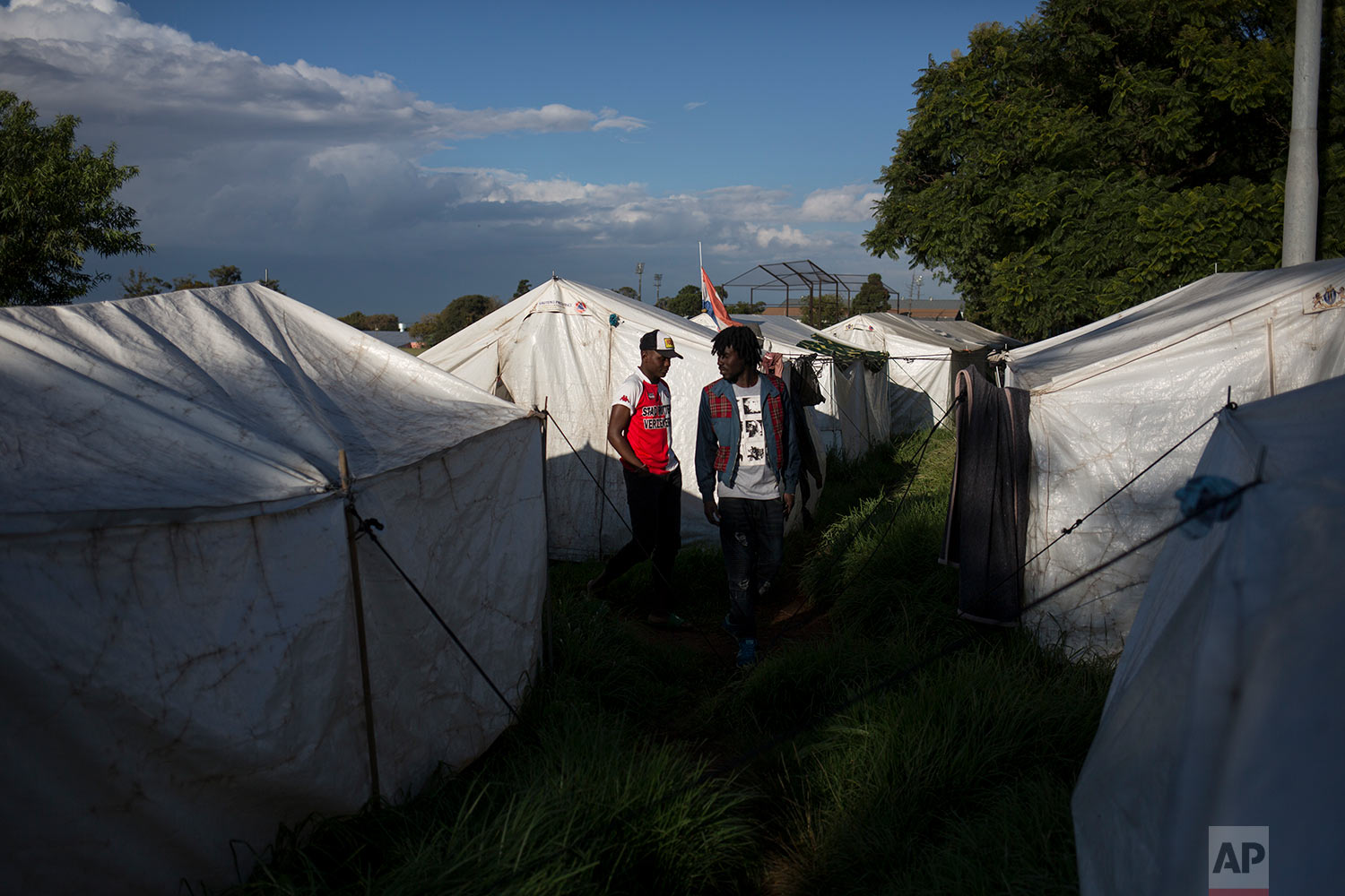 Migrants walk amid tents provided by the city government after they were evicted. April 19, 2018. (AP Photo/Bram Janssen)