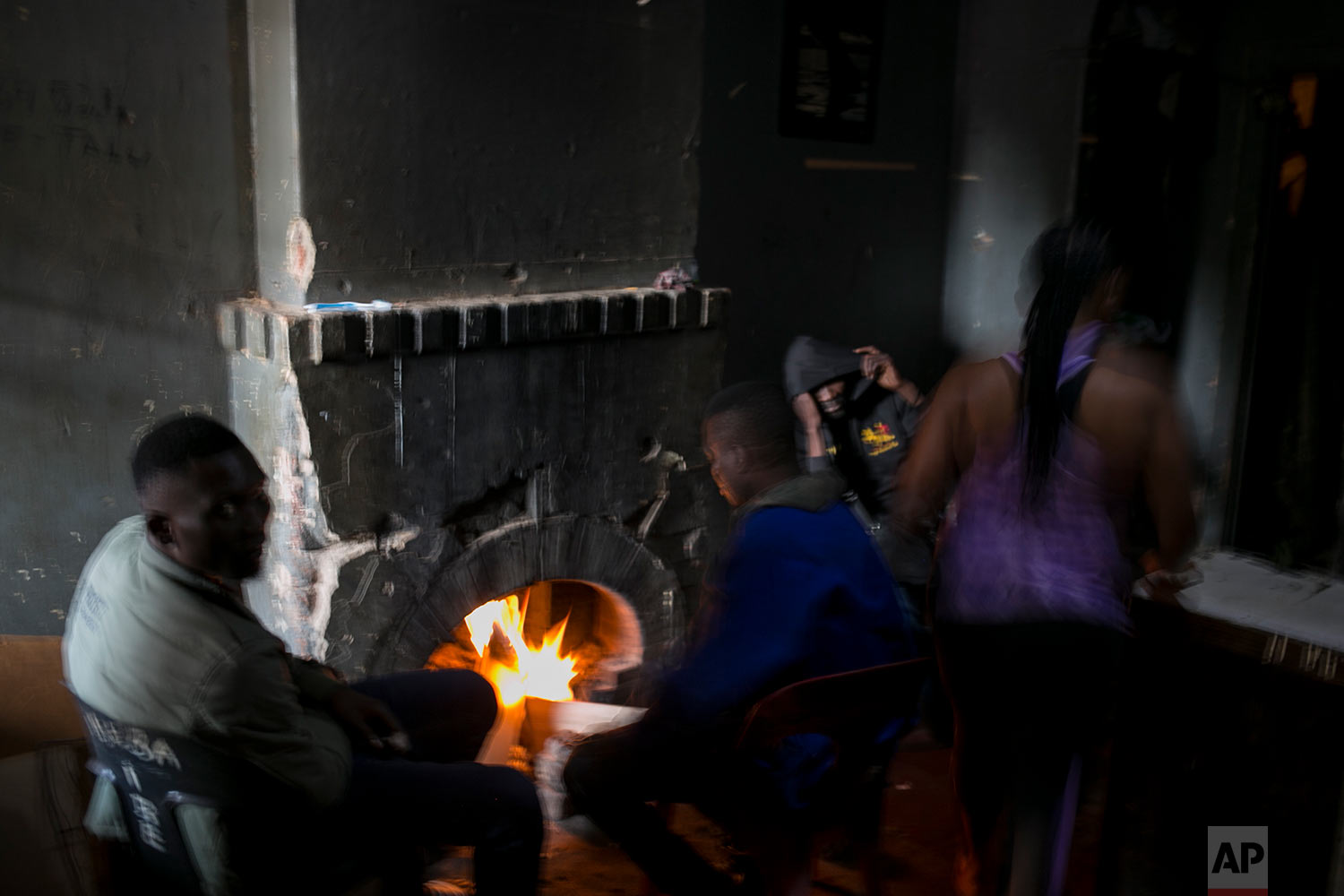 People warm themselves by a fire place in an abandoned building. (AP Photo/Bram Janssen)