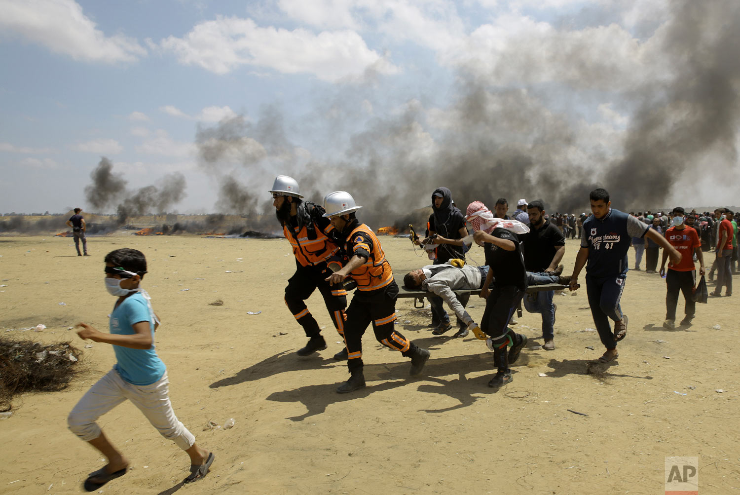 Palestinian medics and protesters evacuate a wounded youth during a protest at the Gaza Strip's border with Israel, east of Khan Younis, Gaza Strip, Monday, May 14, 2018. (AP Photo/Adel Hana)