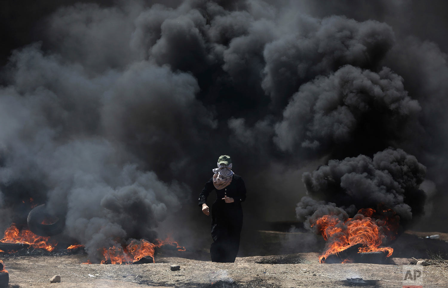 A Palestinian woman walks through black smoke from burning tires during a protest on the Gaza Strip's border with Israel, Monday, May 14, 2018. (AP Photo/Khalil Hamra)