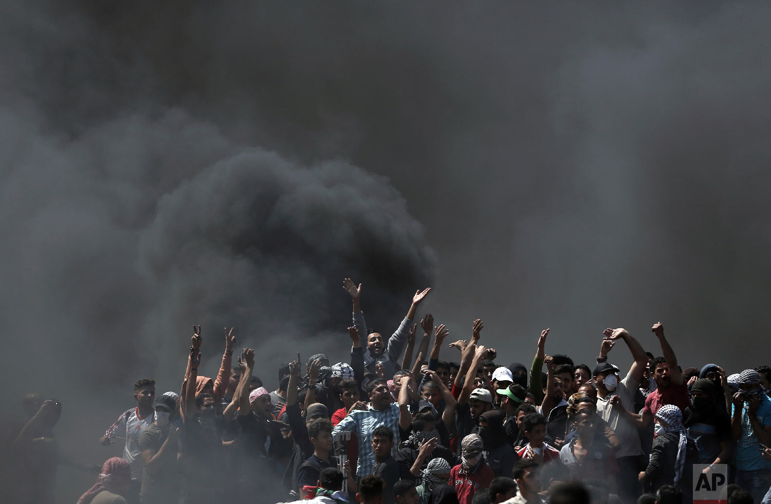 Palestinian protesters chant slogans as they burn tires during a protest on the Gaza Strip's border with Israel, Monday, May 14, 2018. (AP Photo/Khalil Hamra)