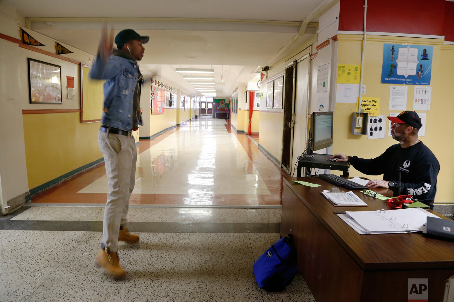 Gerald Smith, student advocate and dean of restorative justice at Chicago's North Lawndale College Prep High School, right, watches after telling a student to do jumping jacks as a consequence for arriving late to school on Thursday, April 19, 2018. Smith also serves as the adult adviser for the school's Peace Warrior group. (AP Photo/Martha Irvine)