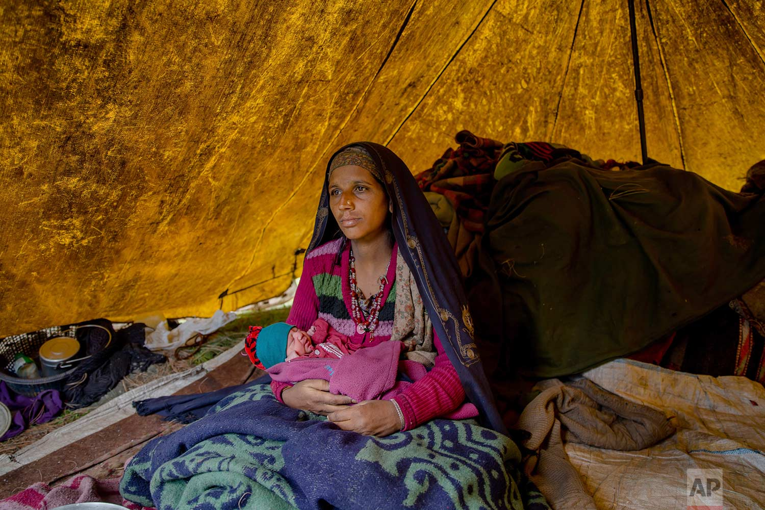 In this May 9, 2018, photo, Nasreen Bano, a Kashmiri nomadic Bakarwal woman poses for pictures along with her new born baby girl inside her tent at a temporary camp in Dubgan, 70 kilometers (43 miles) south of Srinagar, Indian controlled Kashmir. (AP Photo/Dar Yasin)