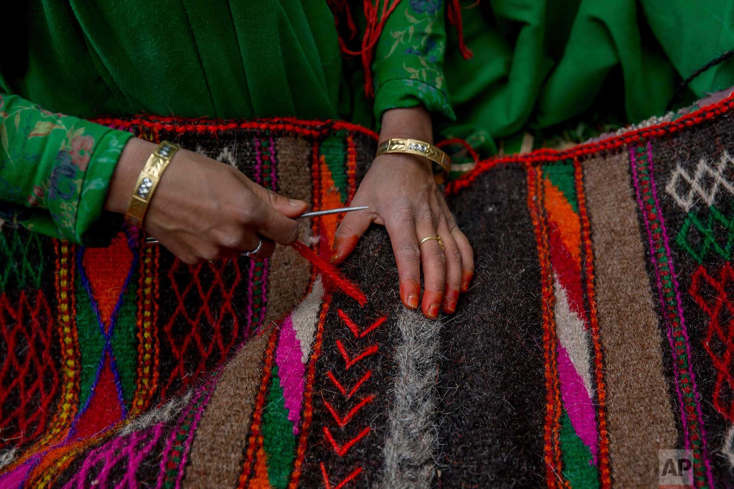 In this May 9, 2018, photo, a Kashmiri nomadic Bakarwal woman decorates a blanket made from goat hair outside her tent in Newa, 29 kilometers (18 miles) south of Srinagar, Indian controlled Kashmir. (AP Photo/Dar Yasin)