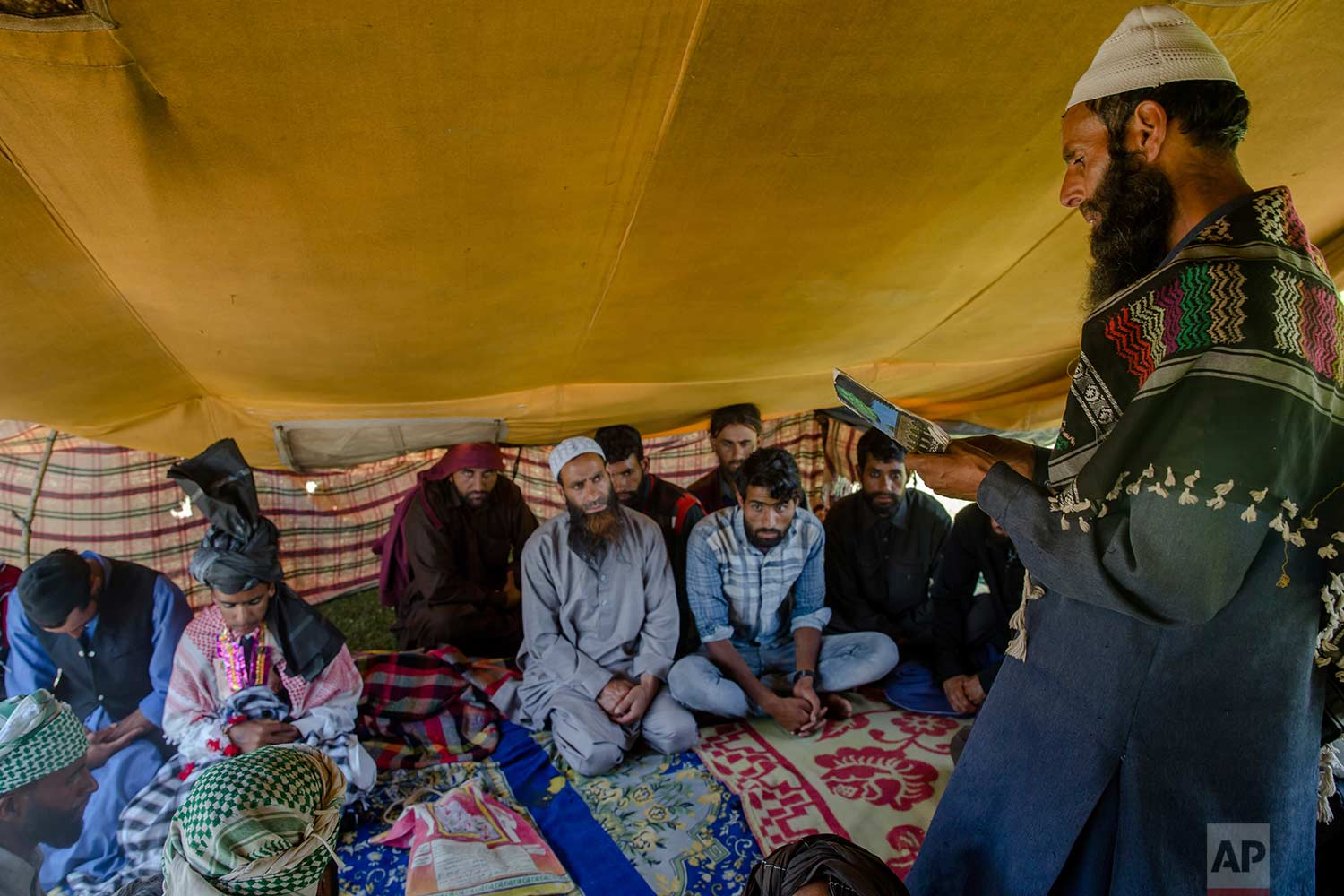 In this May 11, 2018, photo, Kashmiri Bakarwal nomads listen to a sermon delivered by a cleric during a marriage ceremony at a camp in the outskirts of Srinagar, Indian controlled Kashmir. (AP Photo/Dar Yasin)