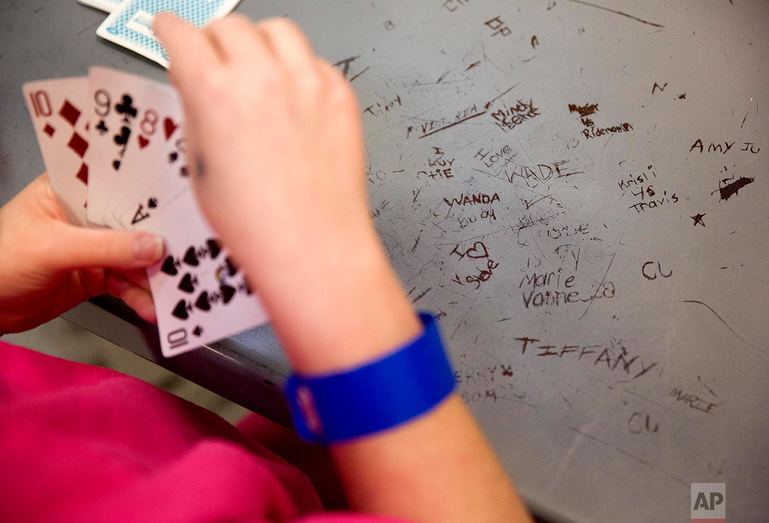 Names are etched in a metal table as inmates play cards in the Campbell County Jail in Jacksboro, Tenn., Thursday, March 15, 2018. (AP Photo/David Goldman)