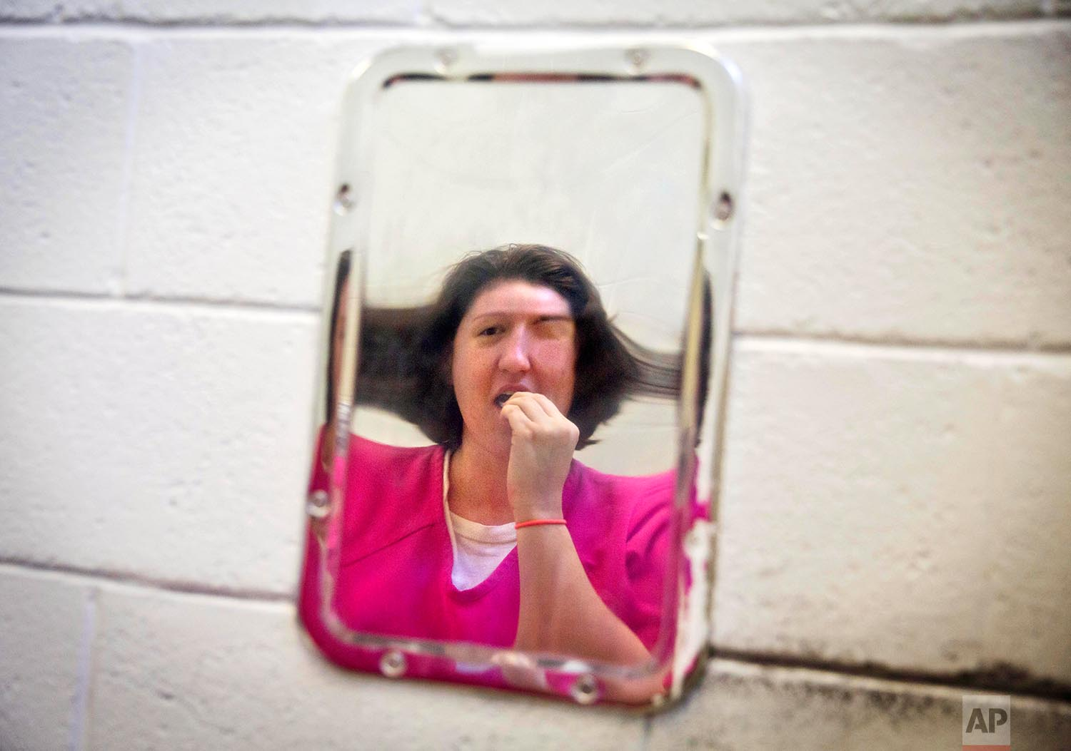 Samantha Marlow brushes her teeth while looking in a distorted metal mirror in her cell at the Campbell County Jail in Jacksboro, Tenn., Tuesday, May 8, 2018. (AP Photo/David Goldman)