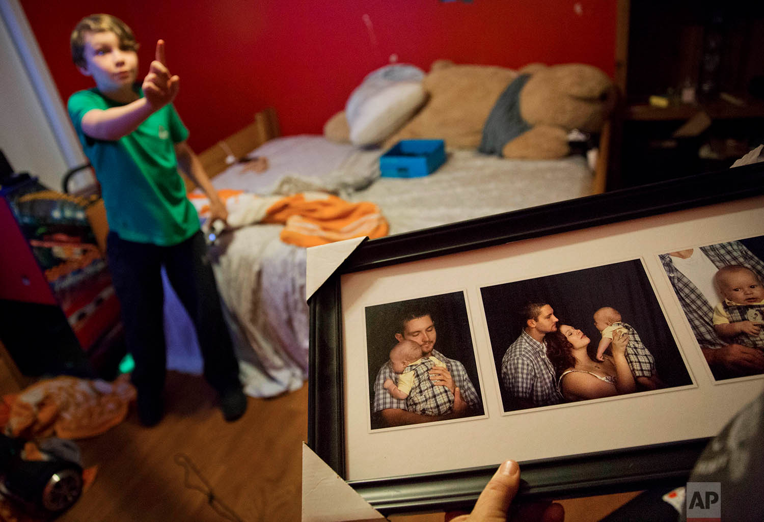 """Eddy Sweat, looks at baby photos of his grandson Robby Wilson, who is standing on the left, in Jacksboro, Tenn., Monday, April 23, 2018. The absence of his mother, Krystle Sweat, has taken its toll on Robby, says his grandmother, Cathy Sweat. """"Even at his happiest,"""" she says, """"he's not happy."""" (AP Photo/David Goldman)"""