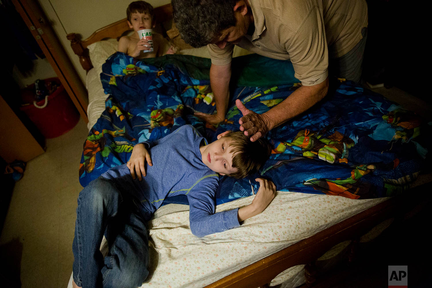 Danny Peters gets his sons Journey, 10, and Chance, 8, ready for bed in LaFollette, Tenn., Wednesday, March 28, 2018, as he cares for them while his ex-wife and the boys' mother, Crystal French, serves time in the Campbell County Jail. (AP Photo/David Goldman)