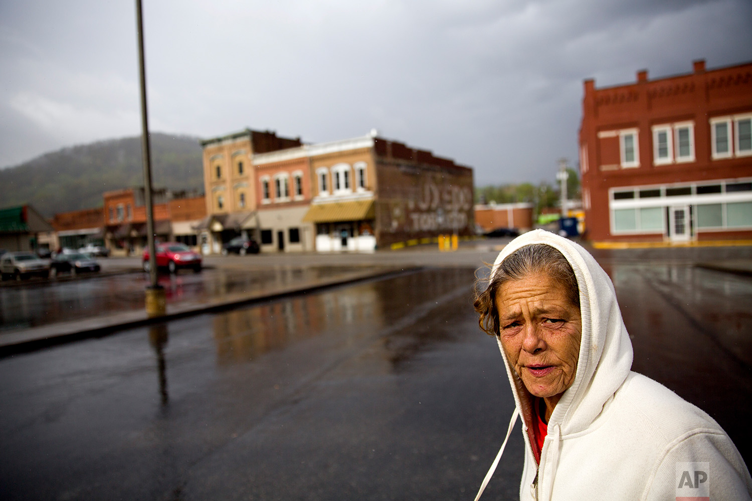 Tammy Perry, 53, walks down a street in LaFollette, Tenn., where she is currently staying with an older man after getting out of jail, Monday, April 23, 2018. Perry still struggles with drug addiction and says she exchanges sex for drugs or money to support her addiction. (AP Photo/David Goldman)
