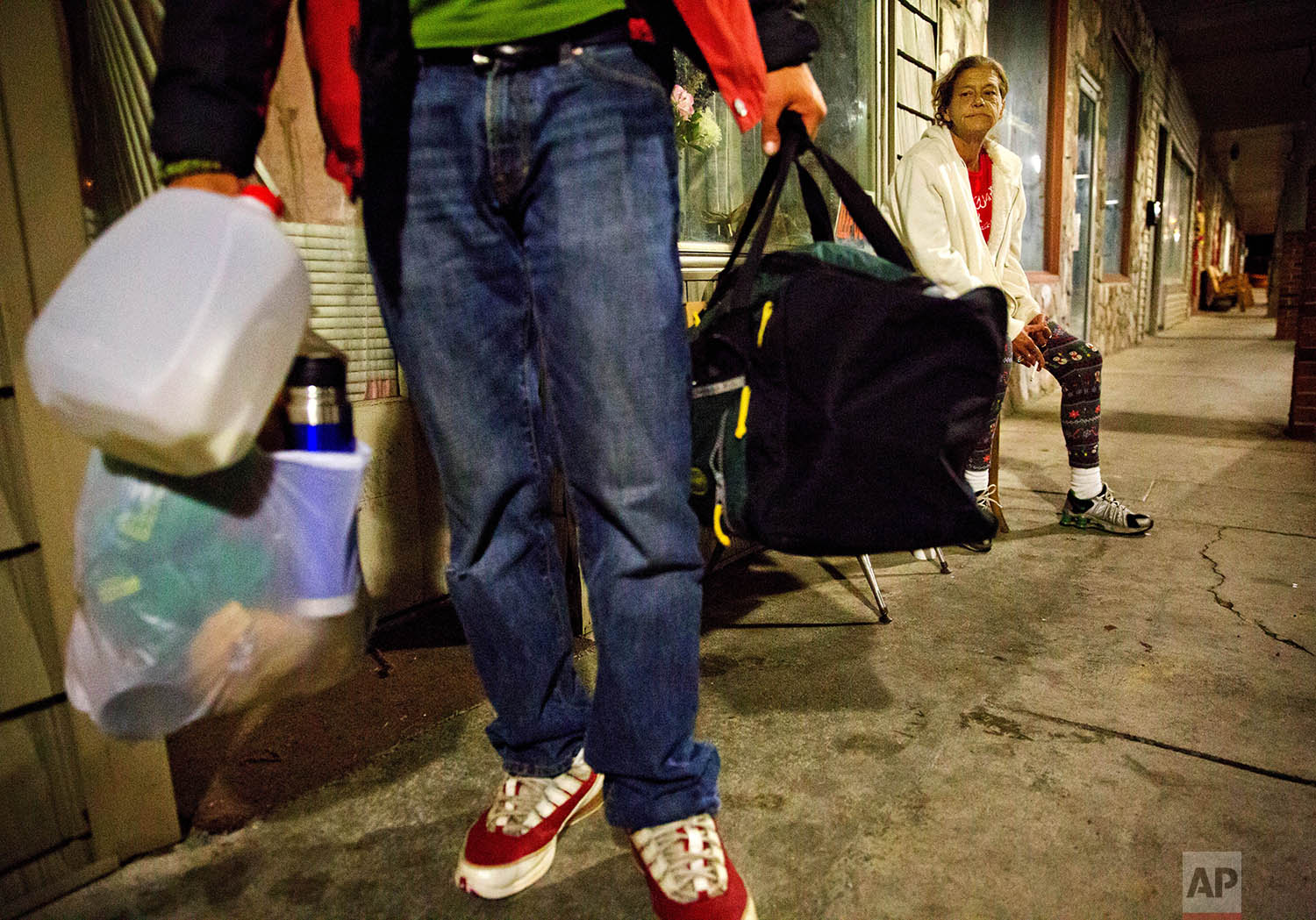 Tammy Perry sits outside the apartment she is staying in after getting released from jail, as a homeless friend, who was kicked out by the tenant, walks away, in LaFollette, Tenn., Monday, April 23, 2018. (AP Photo/David Goldman)