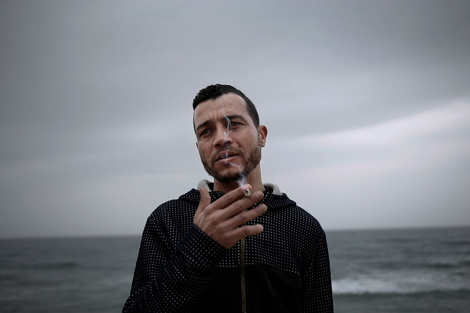 In this Saturday, April 14, 2019 photo, Ahmed Ayouby, 32, smokes a cigarette at the beach where migrants leave for Italy, in Ras Jabal, Tunisia. (AP Photo/Nariman El-Mofty)