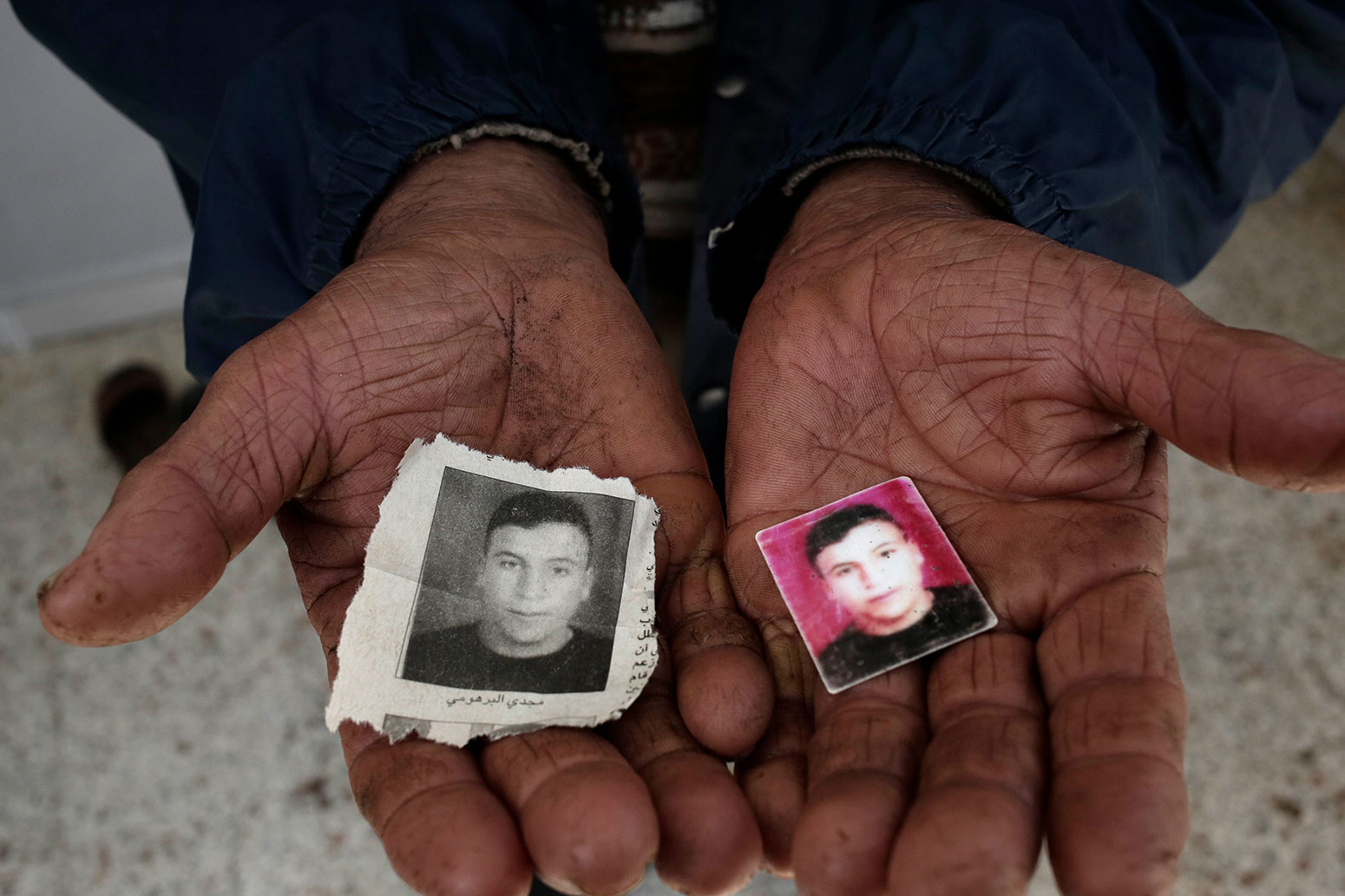 This Thursday, April 12, 2018 photo, the father of Majdi Al Barhoumi, who went missing in 2011, holds photos of him at their home in Ras Jebel, Tunisia. (AP Photo/Nariman El-Mofty)