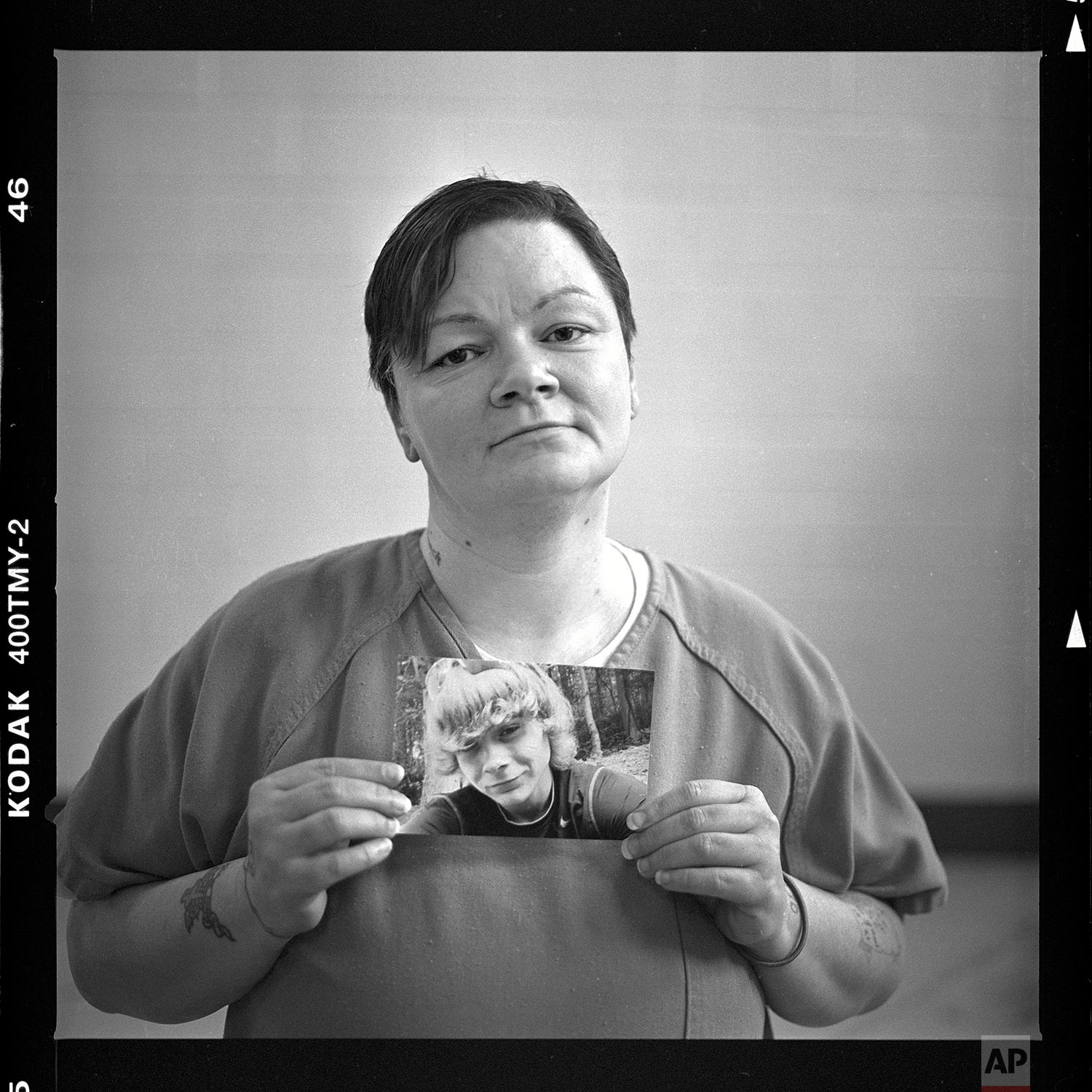 """Mary Sammons, age 41, holds a picture of her son, Micah, 20, who was murdered March 23, as she is photographed in her cell at the Campbell County Jail in Jacksboro, Tenn., Wednesday, April 18, 2018. Sammons suspects her son's murder was drug-related. """"I always pictured my kids burying me, not me having to bury my children. Young kids are losing their life over bad dope. This is crazy. It's so not worth it. He was a pretty boy. He was beautiful.""""(AP Photo/David Goldman)"""