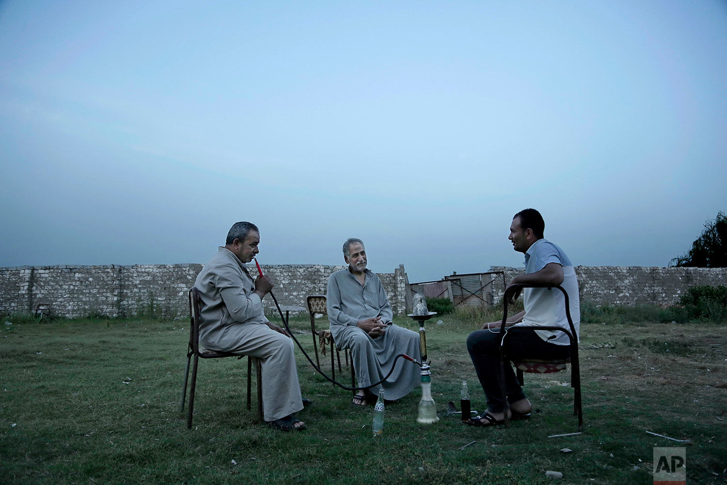 Men in Salah's hometown smoke a water pipe and chat. (AP Photo/Nariman El-Mofty)