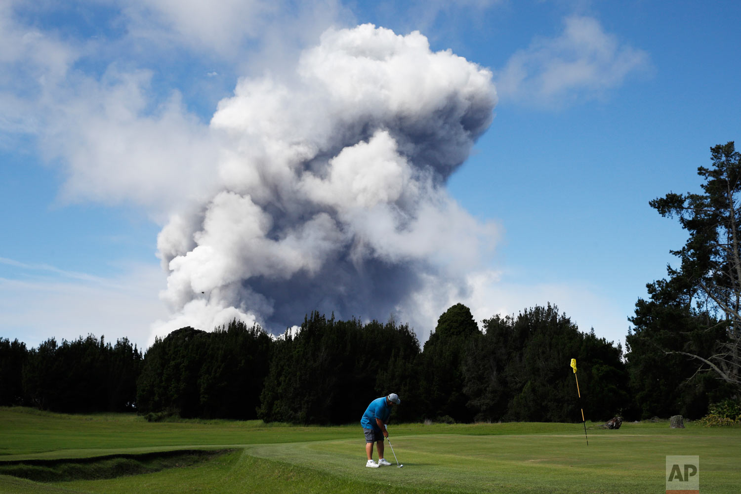 Doug Ralston plays golf in Volcano, Hawaii, as a huge ash plume rises from the summit of the Kiluaea volcano Monday, May 21, 2018. Lava from Hawaii's Kilauea volcano poured into the sea and set off a chemical reaction that created giant clouds of acid and fine glass particles. (AP Photo/Jae C. Hong)
