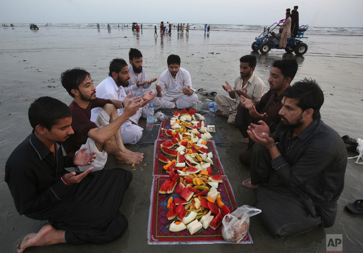 People pray prior to breaking their Ramadan fast at Clifton Beach in Karachi, Pakistan, Saturday, May 19, 2018. Muslims throughout the world are celebrating Ramadan, the holiest month in the Islamic calendar, refraining from eating, drinking, smoking and sex from sunrise to sunset. (AP Photo/Fareed Khan)
