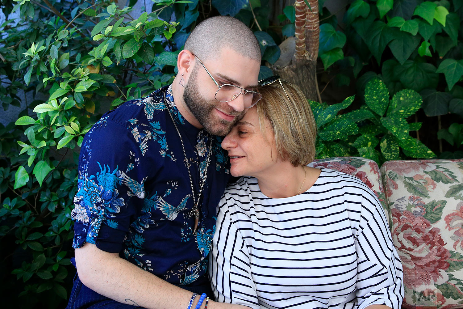 In this picture taken Saturday, May 12, 2018, Elias, 24, who goes by the stage name of Melanie Coxxx hugs his mother Valerie at a restaurant during the launch event of Beirut Pride week in Beirut, Lebanon. (AP Photo/Hassan Ammar)