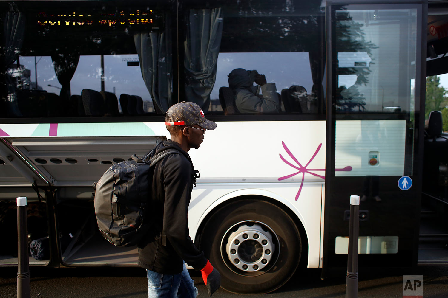A migrant walks toward a bus that will transport him to a gymnasium during the evacuation of a makeshift camp, in Paris, Wednesday, May 30, 2018. (AP Photo/Thibault Camus)