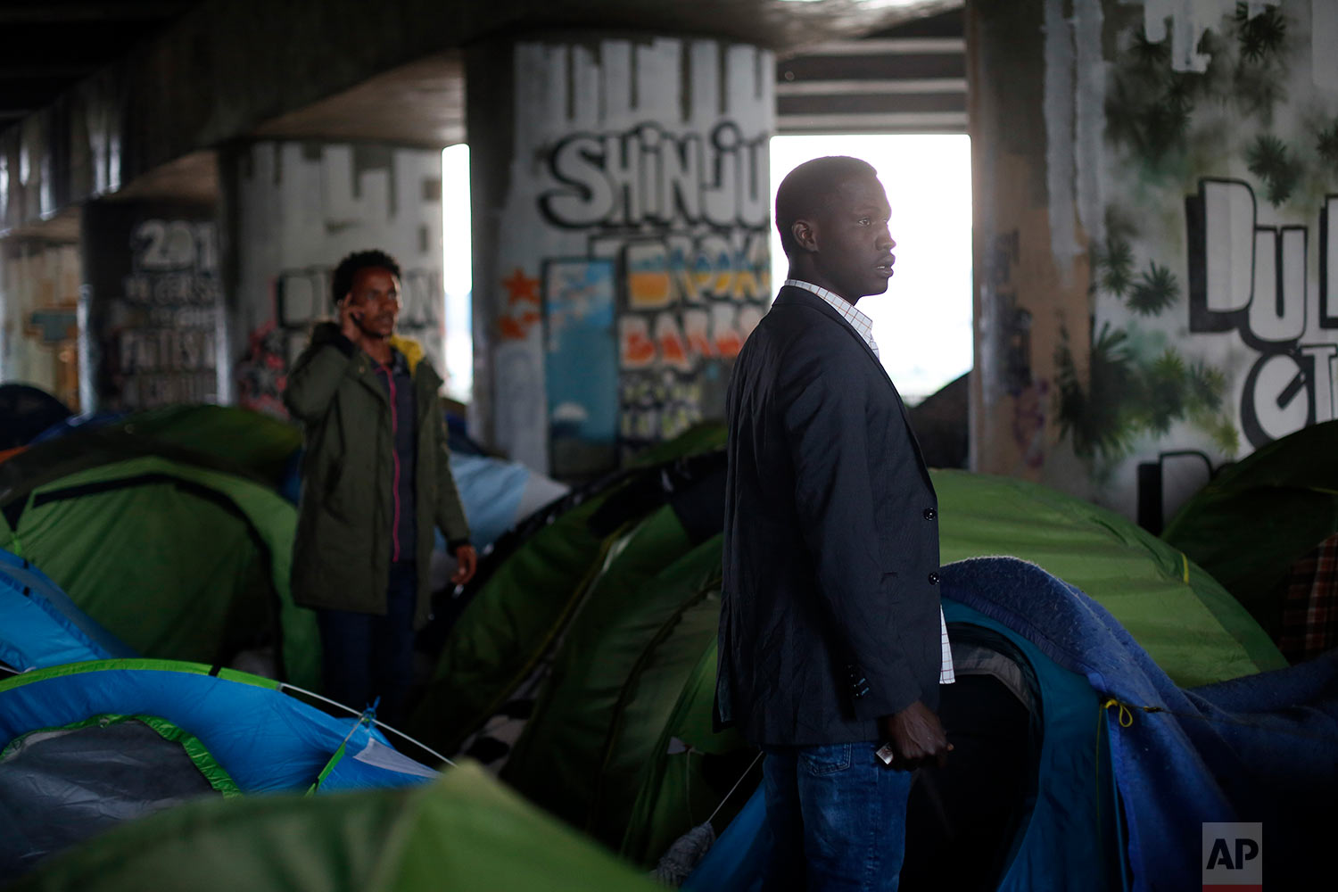 Migrants stand in a makeshift camp during its evacuation, in Paris, Wednesday, May 30, 2018. (AP Photo/Thibault Camus)