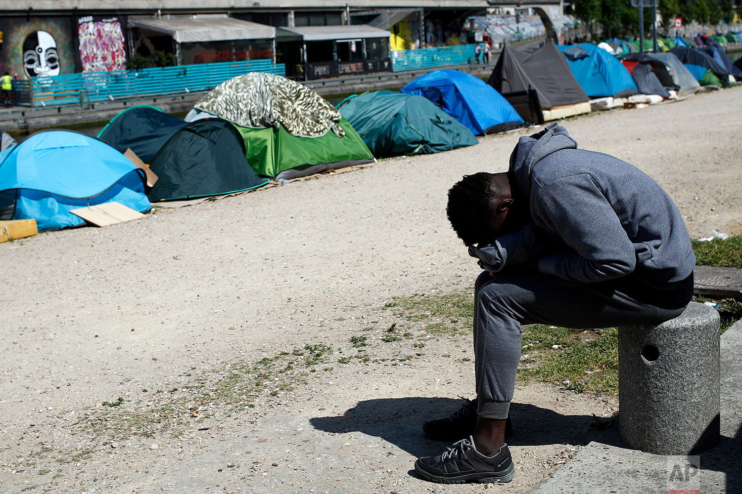 A migrant takes a nap near tents where asylum seekers have set up a makeshift camp alongside the Canal Saint-Martin, in Paris, Friday, May 18, 2018. (AP Photo/Francois Mori)