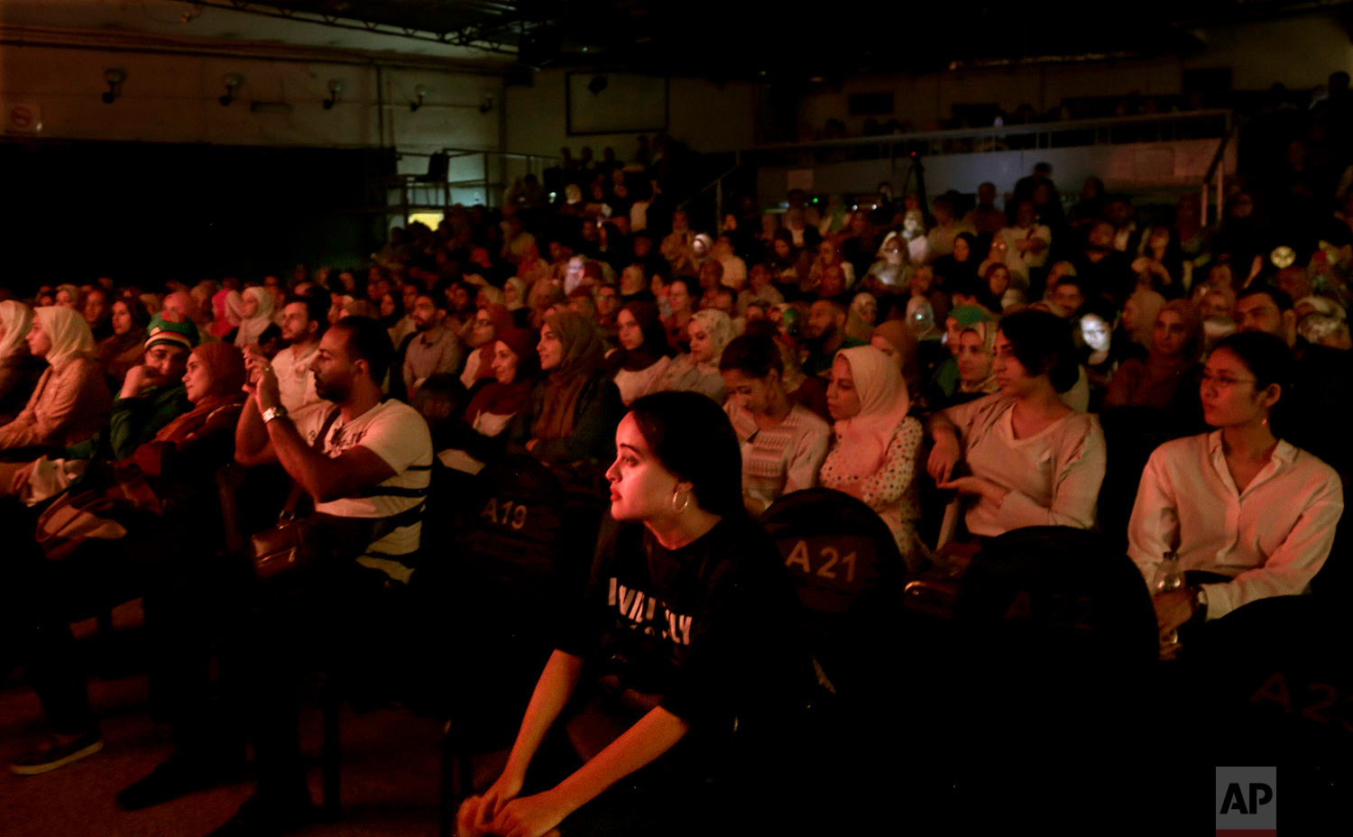 People watch a marionette performance showing Umm Kalthoum, the most famed singer of classical Arabic music, marionettes made by Egyptian artist Mohamed Fawzi Bakkar, at the El Sawy Cultural Center, in Cairo, Egypt, May 3, 2018 . (AP Photo/Nariman El-Mofty)