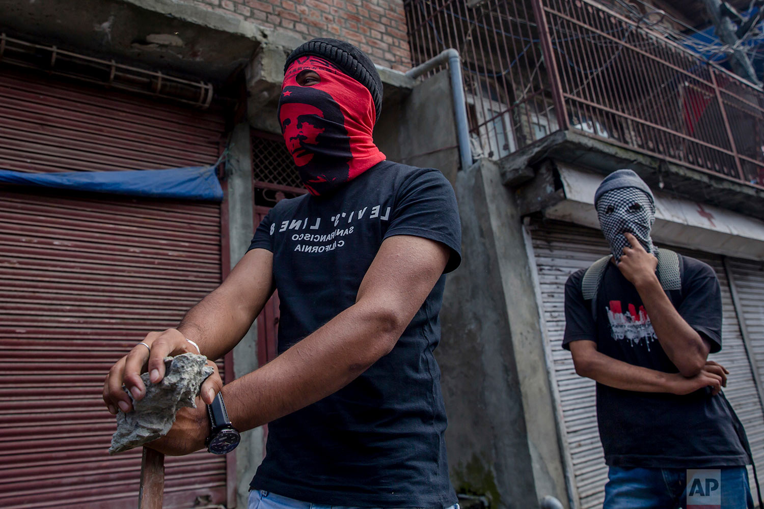 A masked Kashmiri protesters holds a rock as he looks towards the direction of standing policemen in Srinagar, Indian controlled Kashmir, Friday, June 1, 2018. (AP Photo/Dar Yasin)