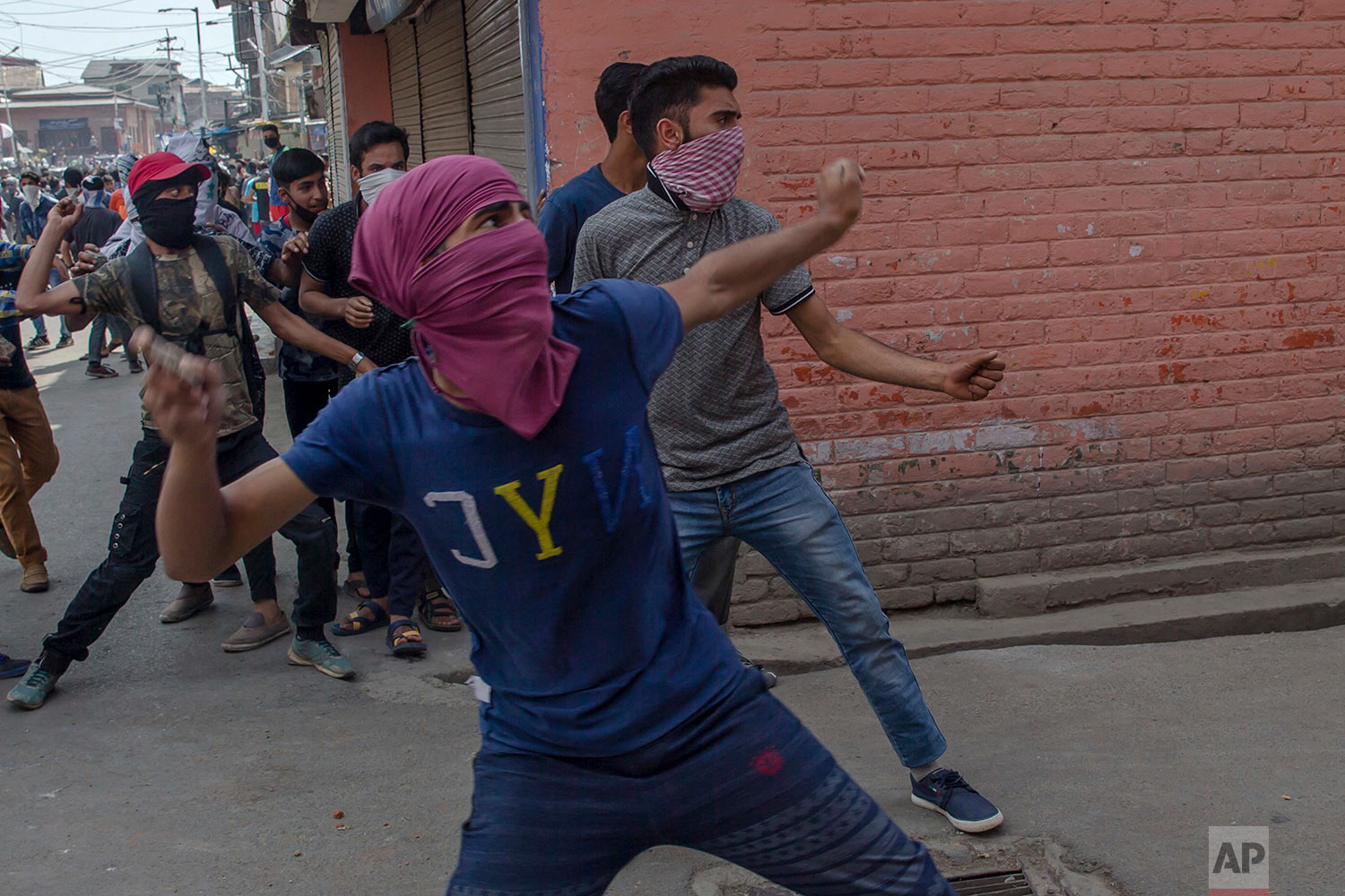 Kashmiri Protesters throw rocks and bricks at policemen in Srinagar, Indian controlled Kashmir, Friday, June 1, 2018. (AP Photo/Dar Yasin)