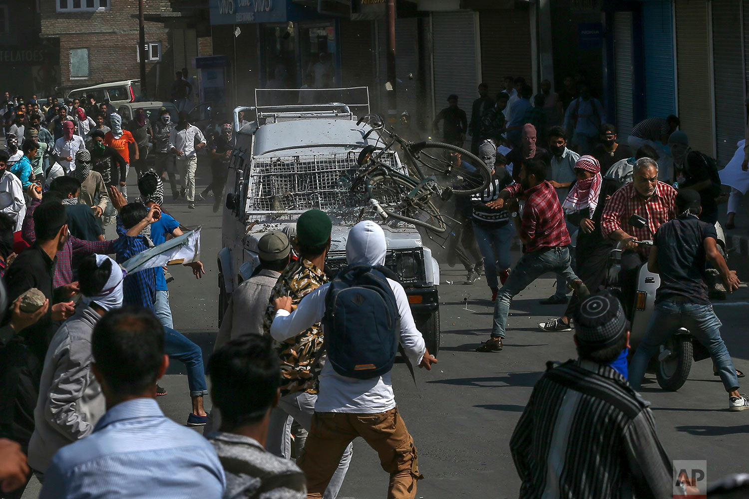 Kashmiri Protesters throw rocks, bricks and a cycle on an Indian paramilitary vehicle in Srinagar, Indian controlled Kashmir, Friday, June 1, 2018. (AP Photo/Dar Yasin)