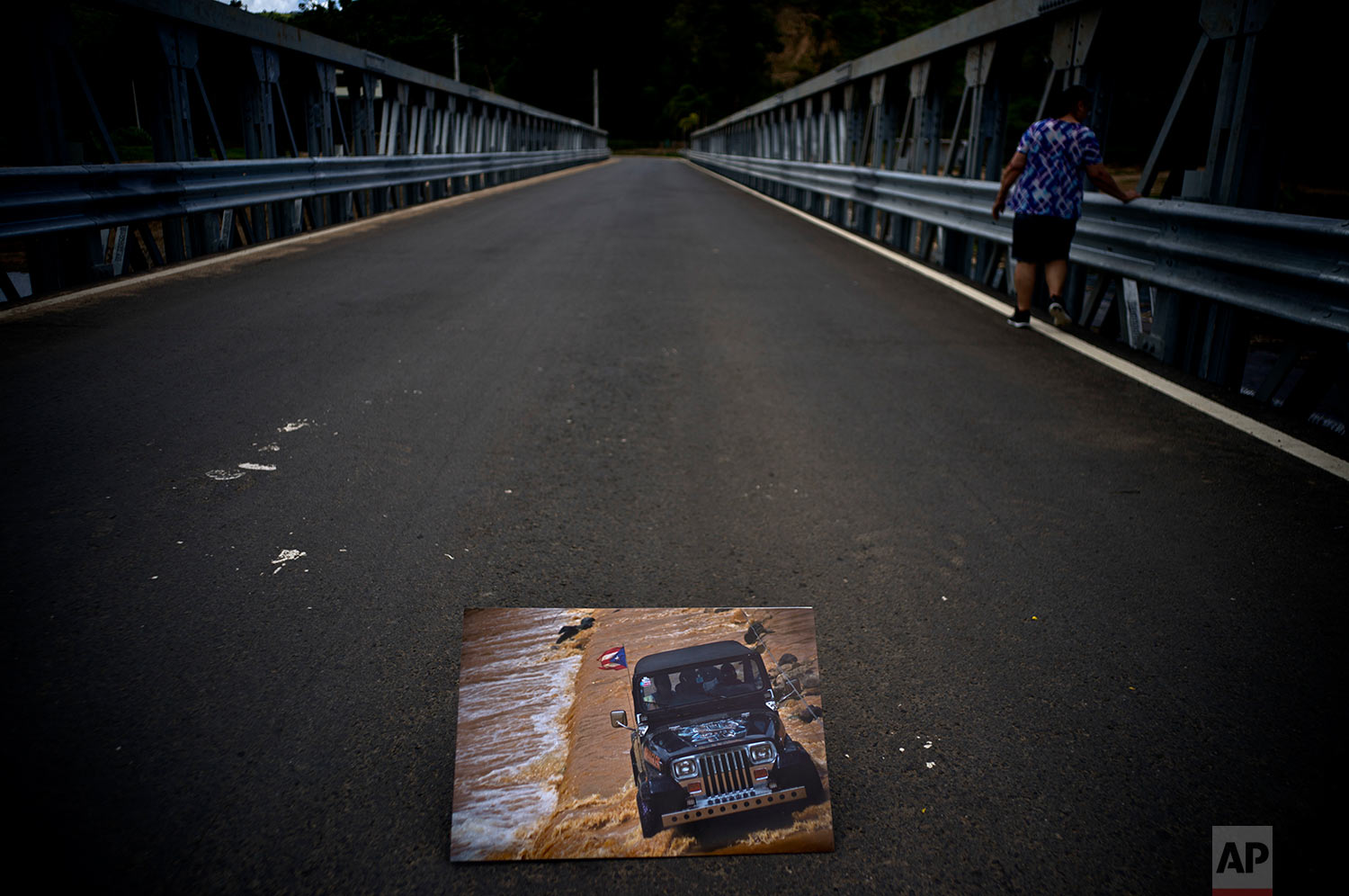 A printed photograph placed on a newly built bridge, shows a jeep crossing a river on Oct. 7, 2017, after an old bridge was washed out in the San Lorenzo neighborhood of Morovis, Puerto Rico, May 26, 2018.(AP Photo/Ramon Espinosa)