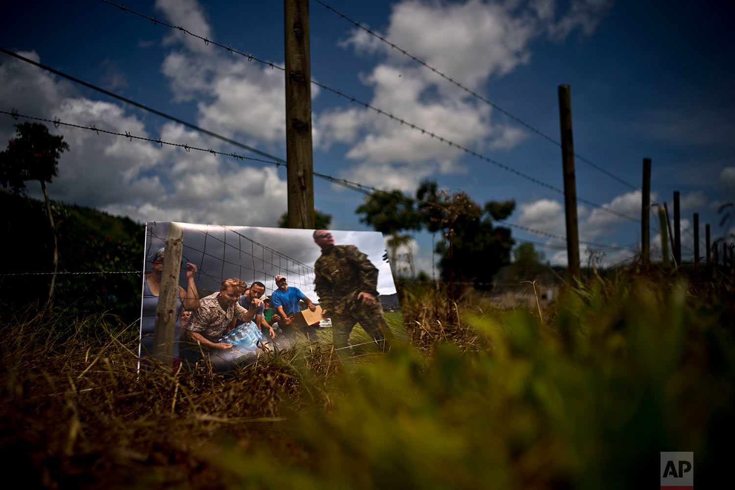 A printed photograph taken on Oct. 7, 2017 sits at the same spot where Puerto Rican National Guards delivered food and water to desperate residents in the aftermath of Hurricane Maria in the San Lorenzo neighborhood of Morovis, Puerto Rico, May 26, 2018. (AP Photo/Ramon Espinosa)
