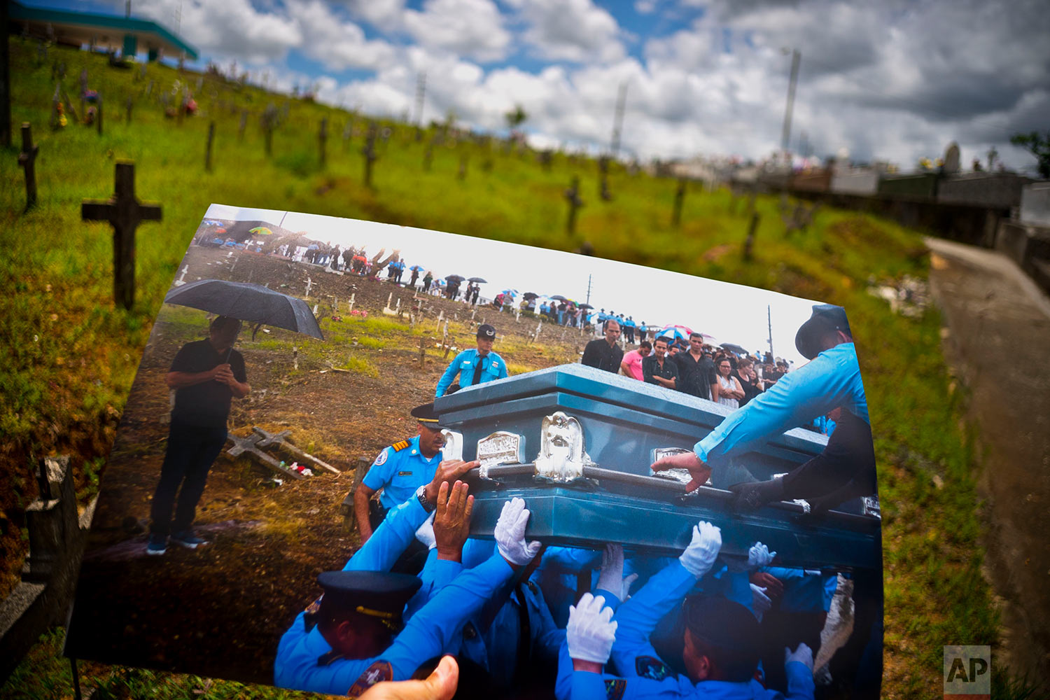 A printed photo taken on Sept. 29, 2017 showing police lifting the coffin of officer Luis Angel Gonzalez Lorenzo, is shown at the same cemetery in Aguada, Puerto Rico, May 31, 2018. (AP Photo/Ramon Espinosa)