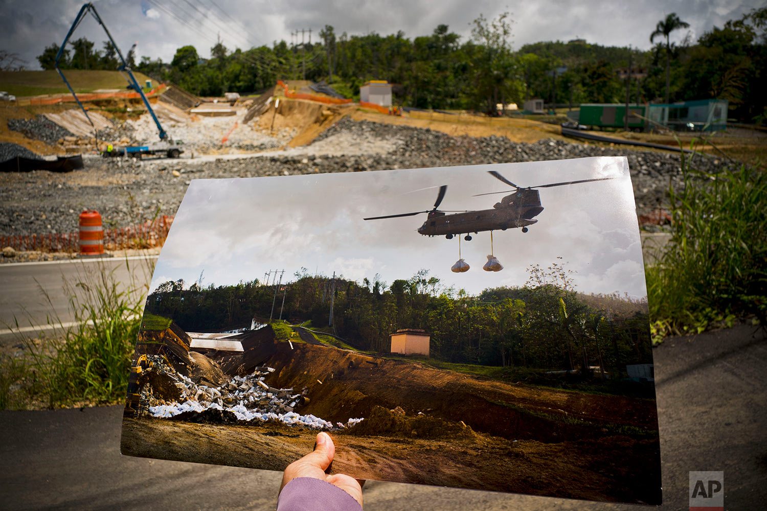 A printed photo taken on Oct. 17, 2017 showing a U.S. army helicopter transporting material to repair the Guajataca Dam, in Quebradillas, Puerto Rico, May 31, 2018. (AP Photo/Ramon Espinosa)