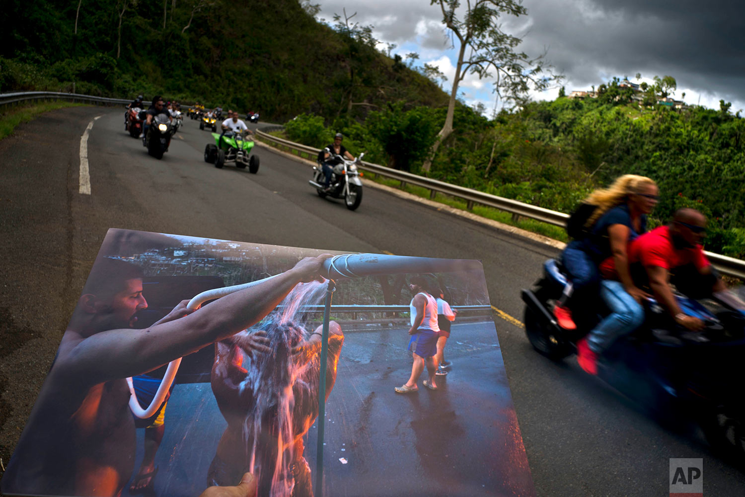 A printed photograph taken on Sept. 28, 2017, is held up at the same spot of the highway, in Naranjito, Puerto Rico, May 27, 2018. (AP Photo/Ramon Espinosa)