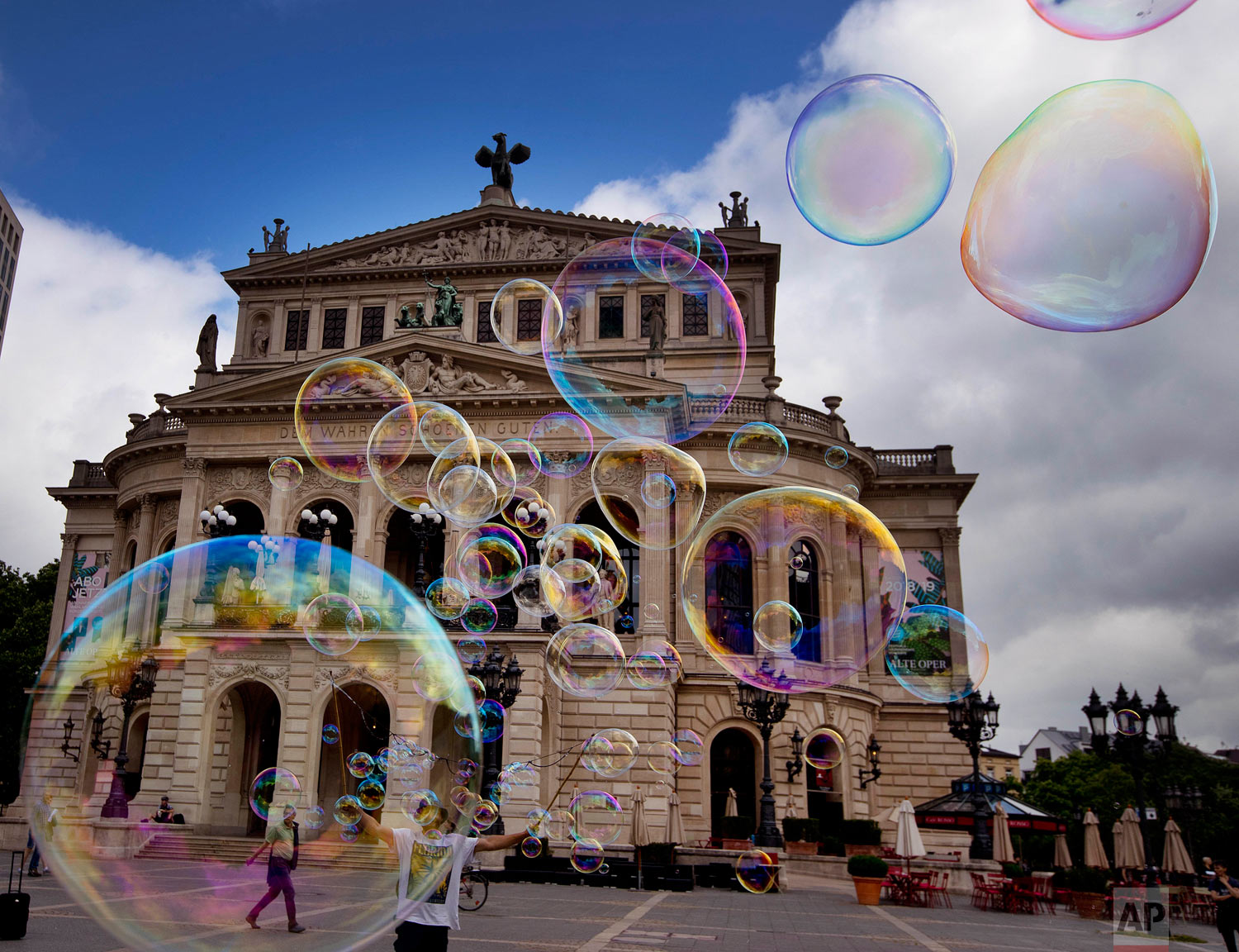 A bubble artist performs with soap bubbles in front of the Old Opera in Frankfurt, Germany, Friday, June 1, 2018. (AP Photo/Michael Probst)