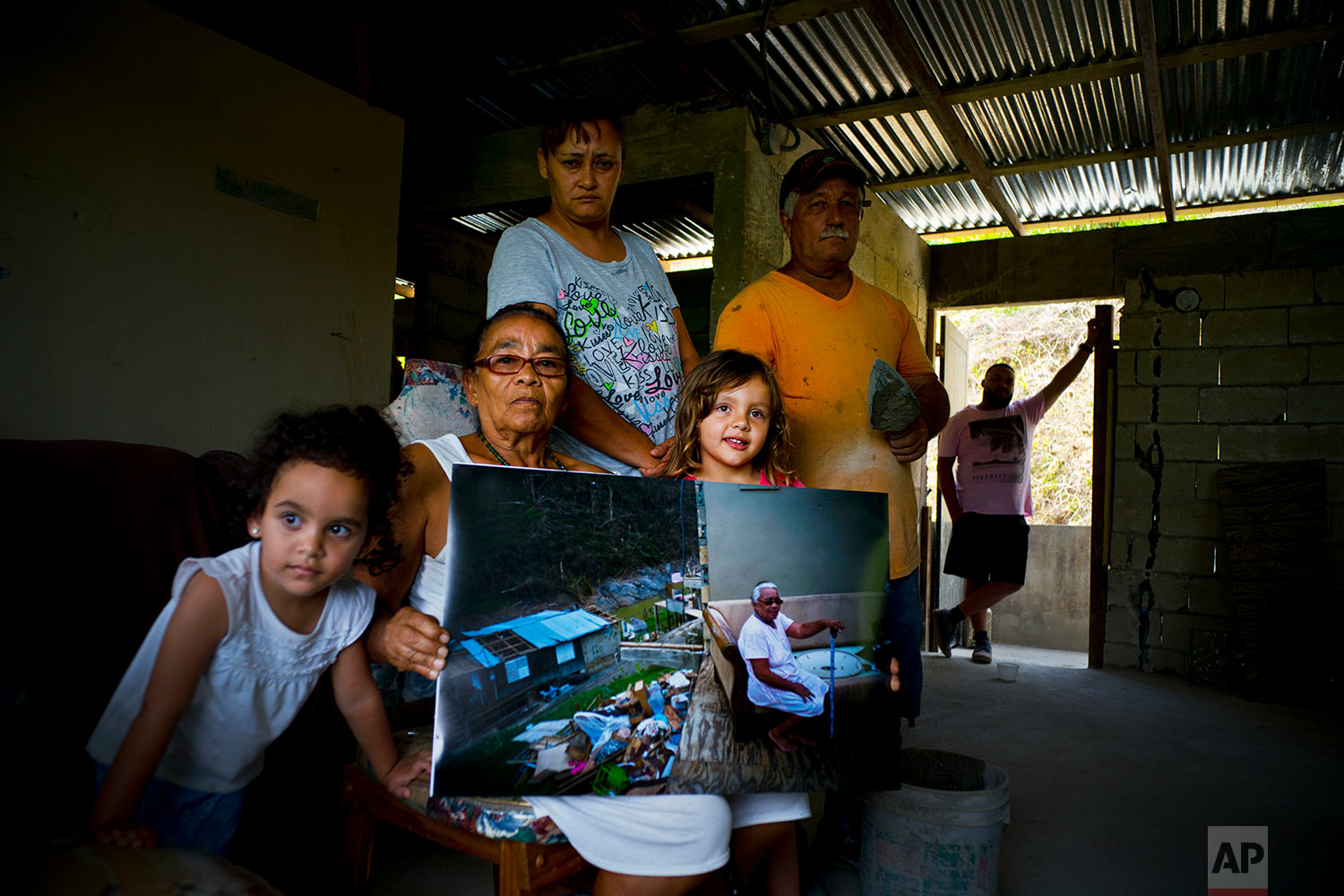 Juana Sostre Vazquez poses with her family and holds a printed photograph of her taken after Hurricane Maria, in the San Lorenzo neighborhood of Morovis, Puerto Rico, May 26, 2018. (AP Photo/Ramon Espinosa)