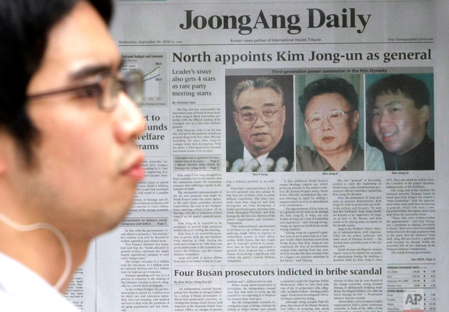 A man walks past a South Korean newspaper bearing photos of North Korean leader Kim Jong Il, center, his late father Kim Il Sung, left, and his youngest son Kim Jong Un, in Seoul, South Korea, on Sept. 29, 2010. (AP Photo/Ahn Young-joon)