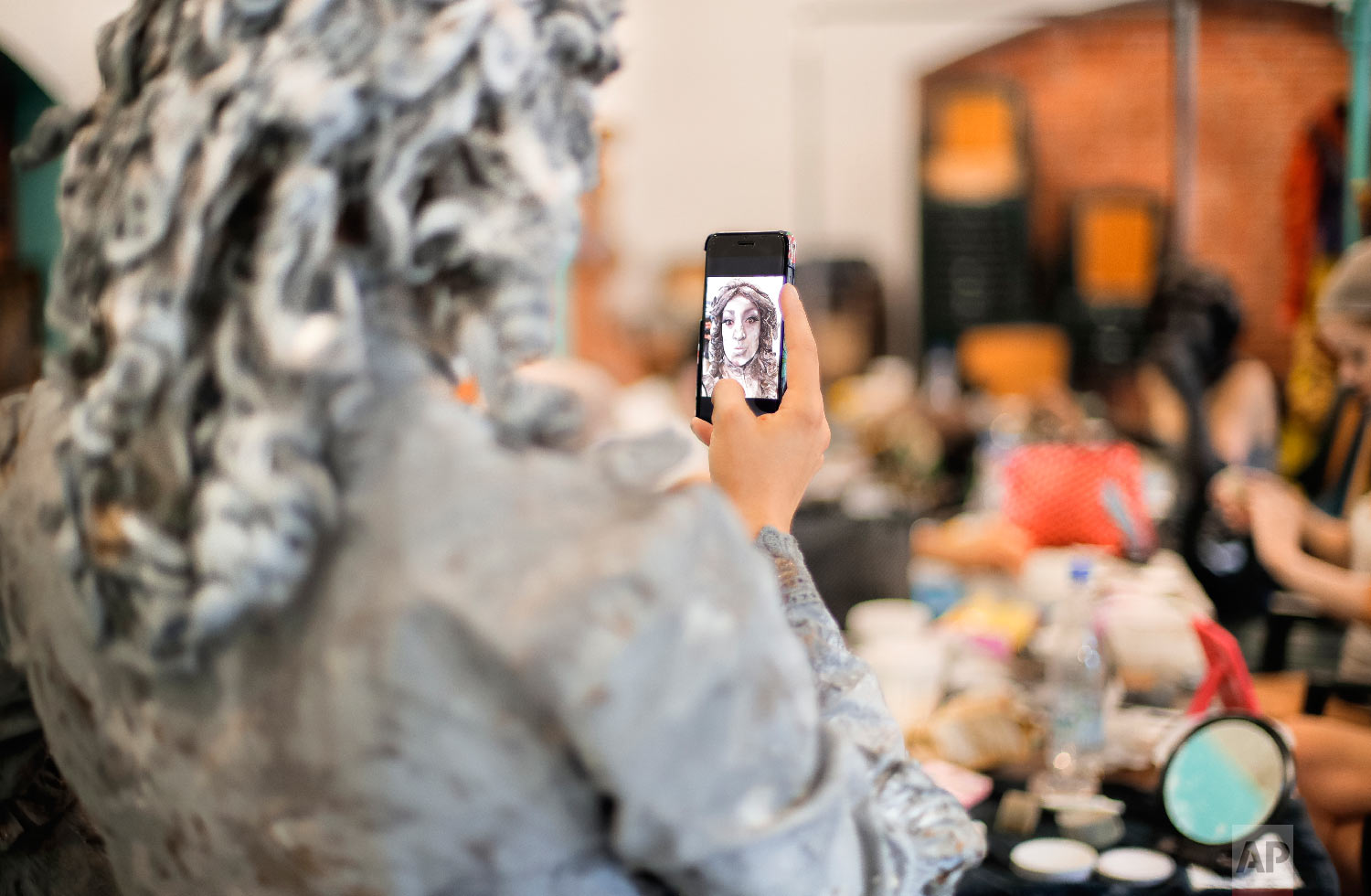 An artist of The Netherlands' Levend Theater takes a selfie before performing her Angel character during the Living Statues International Festival, in Bucharest, Romania on Tuesday, May 22, 2018.(AP Photo/Vadim Ghirda)