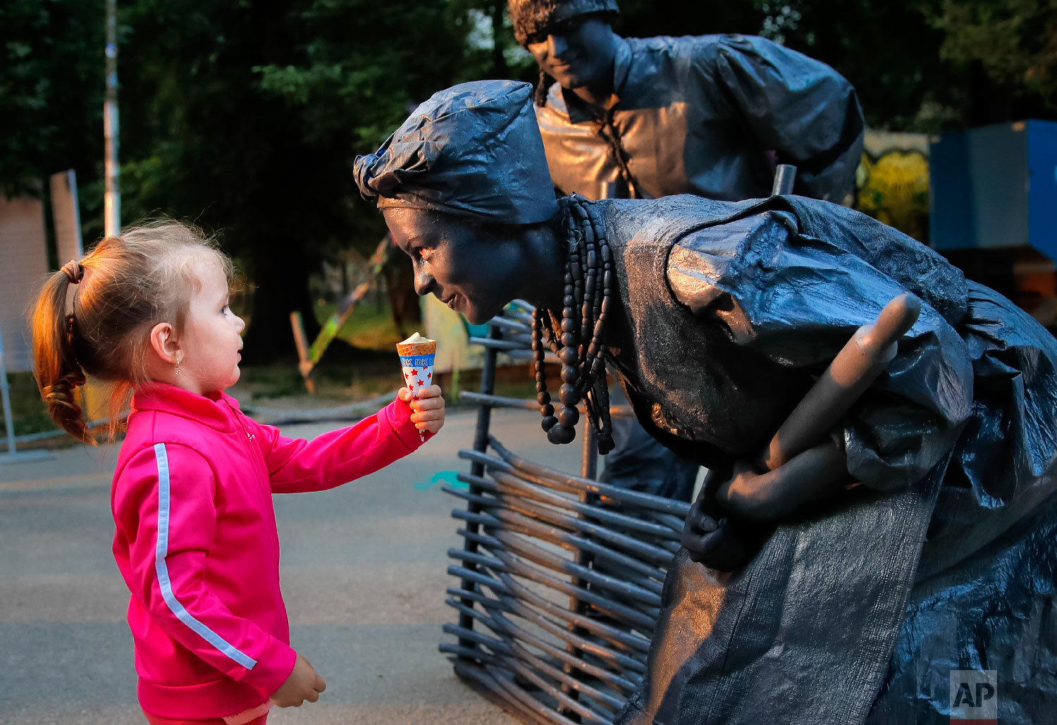 """A child offers ice-cream to artists of Ukraine's Artel Myth theatre performing """"A day in the life of Ukrainians"""" at the Living Statues International Festival, in Bucharest, Romania on Thursday, May 24, 2018. (AP Photo/Vadim Ghirda)"""