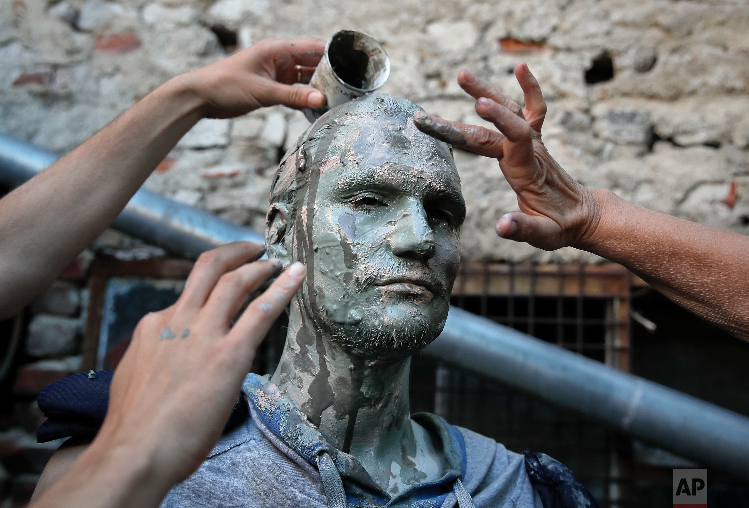 An artist of Romania's Masca theatre has make-up applied to his face before performing at the Living Statues International Festival, in Bucharest, Romania on Tuesday, May 22, 2018,. (AP Photo/Vadim Ghirda)