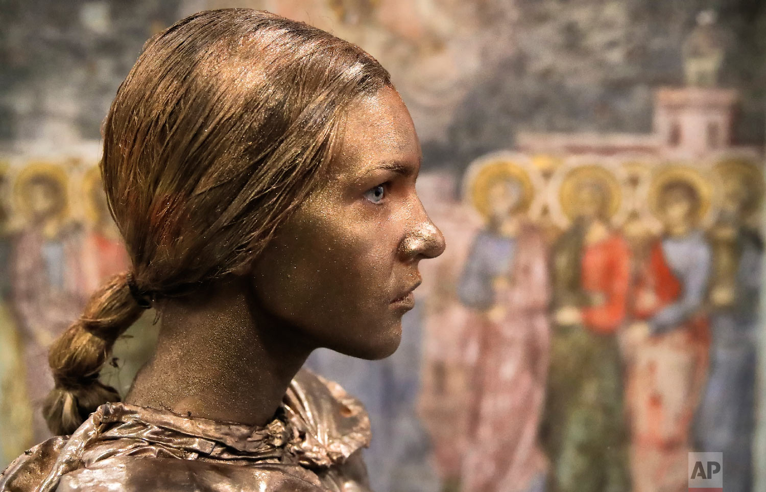 An artist of Ukraine's Artel Myth theatre is backdropped by a religious painting before performing her Yaroslavna character during the Living Statues International Festival, in Bucharest, Romania on Tuesday, May 22, 2018. (AP Photo/Vadim Ghirda)