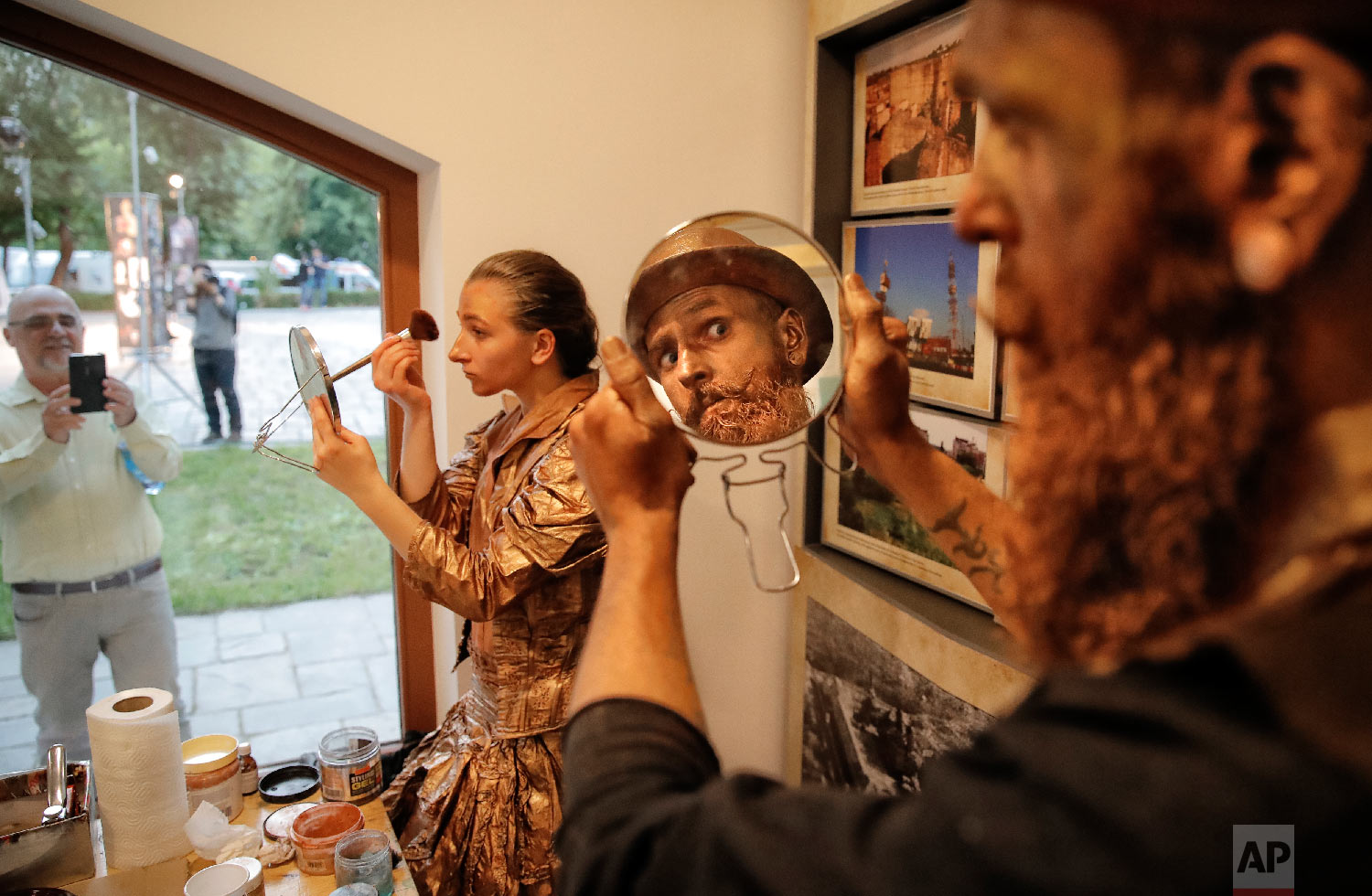 Artists of Ukraine's Artel Myth theatre apply make-up before performing in the Living Statues International Festival, in Bucharest, Romania in Tuesday, May 22, 2018 (AP Photo/Vadim Ghirda)
