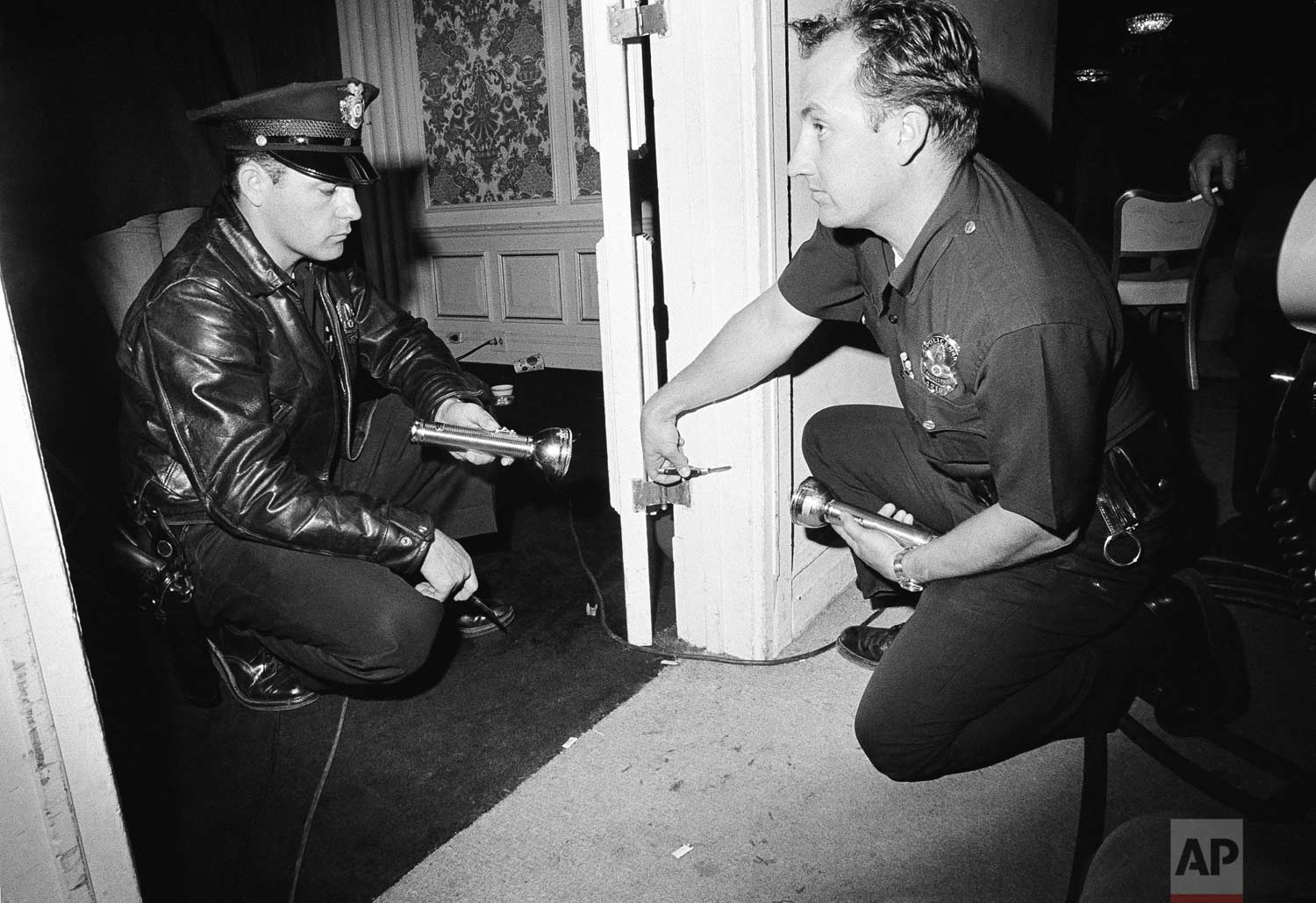 Robert Rozzi, police technician, and Charles Wright, police officer, left, inspect a bullet hole discovered in a door frame in a kitchen corridor of the Ambassador hotel in Los Angeles near where Sen. Robert F. Kennedy was shot and critically wounded June 5, 1968. Bullet is still in the wood. (AP Photo/Dick Strobel)