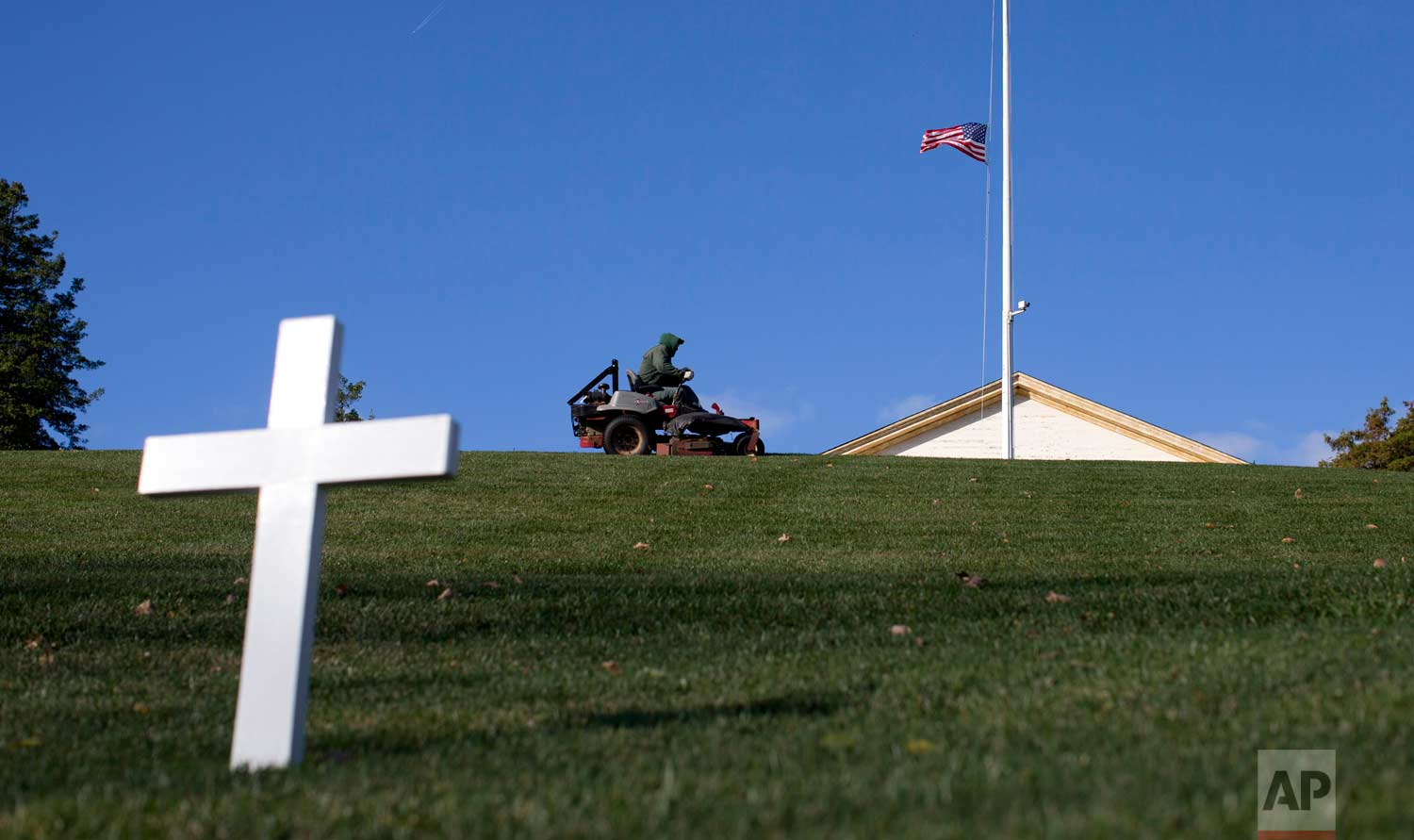 This Nov. 19, 2013 photo shows a cross marking the grave of Robert F. Kennedy as a groundskeeper mows the grass near the Arlington House, right, at Arlington National Cemetery in Arlington, Va. On June 5, 1968, Associated Press Hollywood reporter Bob Thomas was on a one-night political assignment covering Kennedy's victory celebration in the California presidential primary at the Ambassador Hotel in Los Angeles when mayhem unfolded before his eyes. (AP Photo/Carolyn Kaster)