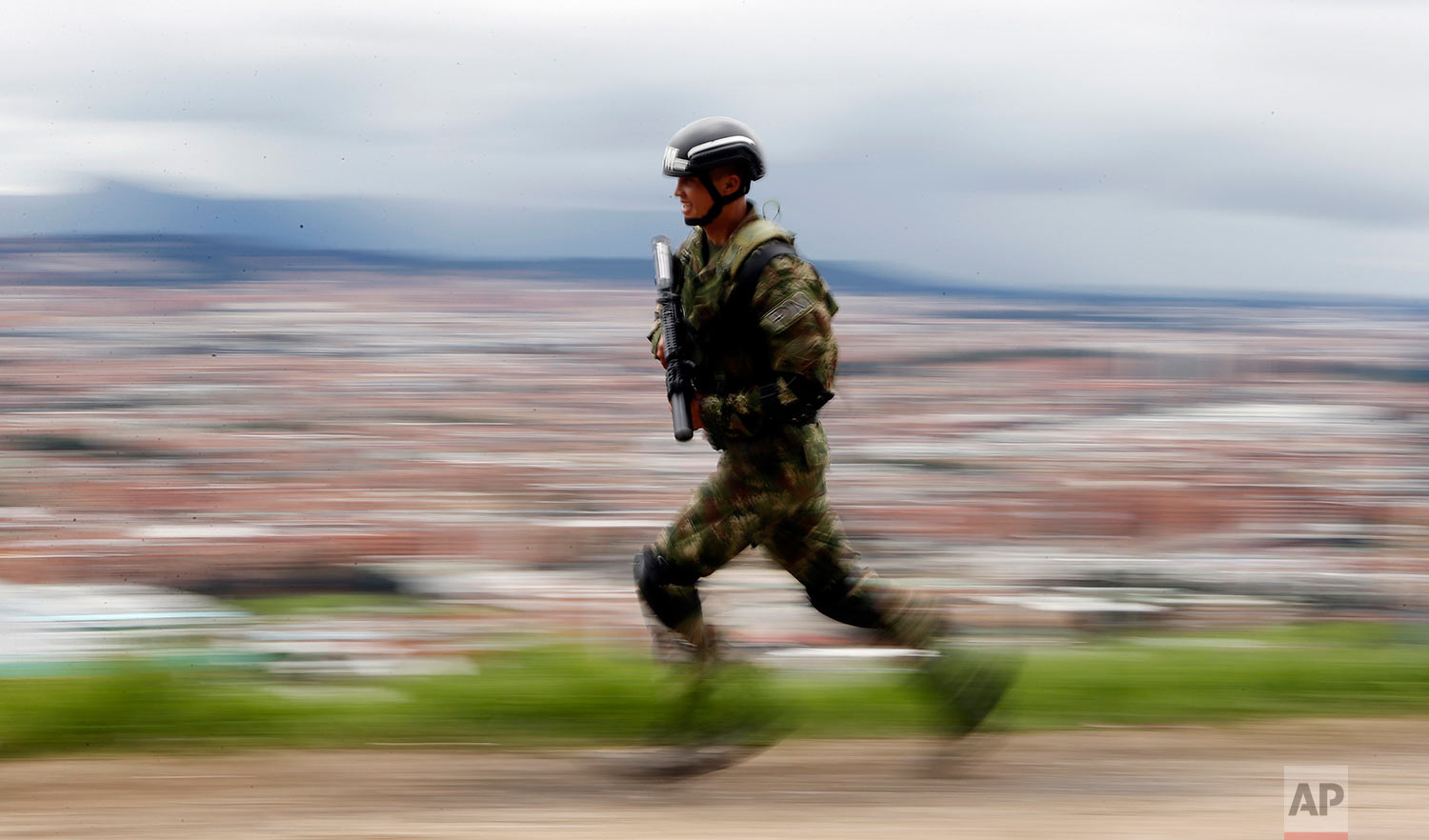 A solider runs to his position to secure a road as part of electoral security ahead of the presidential election on the outskirts of Bogota, Colombia, Saturday, May 26, 2018. (AP Photo/Fernando Vergara)
