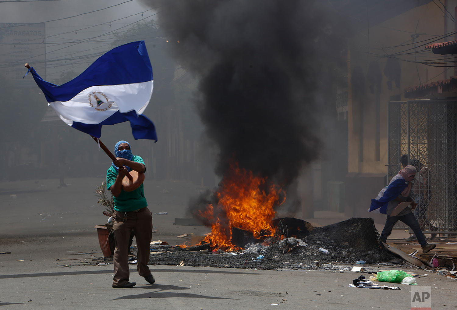 A protestor waves a Nicaraguan national flag at a burning roadblock as protestors clash with police in the Monimbo district of Masaya, Nicaragua, Saturday, May 12, 2018. Protests began in April as students demonstrated against a social security reform. Many are now demanding that President Daniel Ortega and his wife Rosario Murillo leave office. (AP Photo/Alfredo Zuniga)