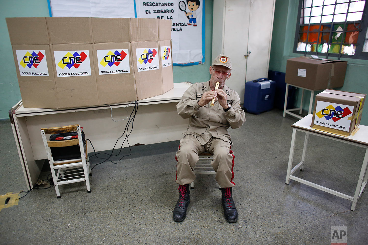 "A Bolivarian Militia member plays the flute at a polling station during the presidential election in Caracas, Venezuela, Sunday, May 20, 2018. Before the government-controlled National Election Council declared current President Nicolas Maduro the overwhelming winner, nations around the world had accused him of taking Venezuela down the path toward ""dictatorship."" (AP Photo/Ariana Cubillos)"