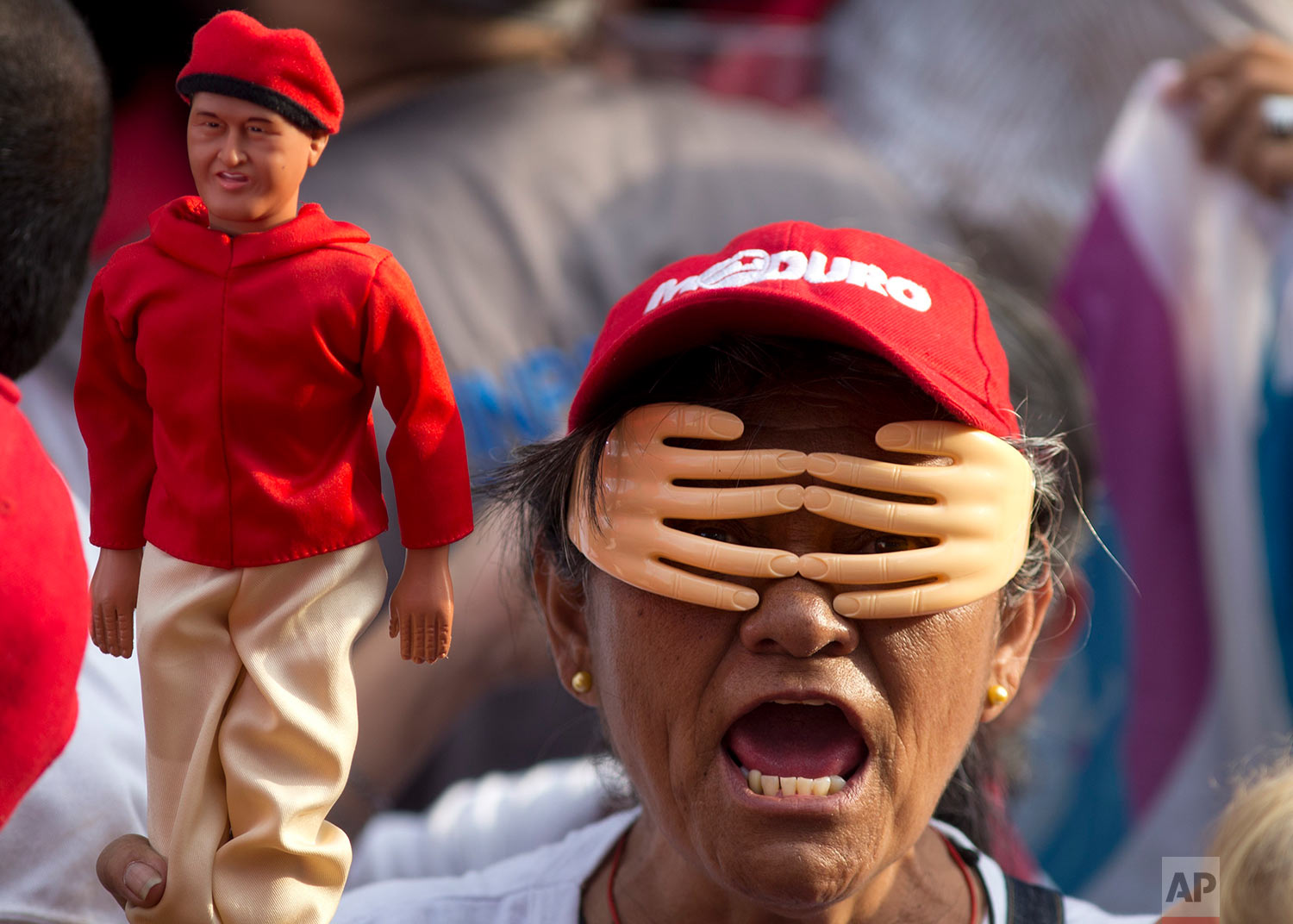 A government supporter holding a doll of Venezuela's late President Hugo Chavez wears a set of plastic hands over her eyes, at a presidential campaign rally for current President Nicolas Maduro in Caracas, Venezuela, Friday, May 4, 2018.  The election registered the lowest turnout in decades — around 46 percent — as many voters stayed home while the opposition warned the election was rigged. (AP Photo/Ariana Cubillos)
