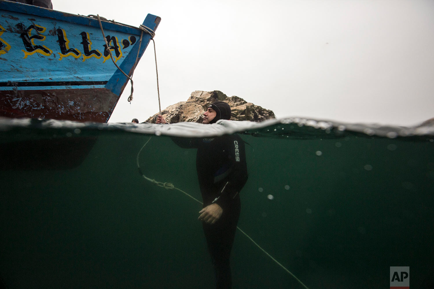 A diver stays afloat in the Pacific Ocean at the end of an exploration excursion of a sunken ship close to the Ancon coast, near Lima, Peru, Sunday, May 27, 2018. The El Ferrol, an old cargo ship, ran aground in 2005 and sank in 2007. (AP Photo/Rodrigo Abd)
